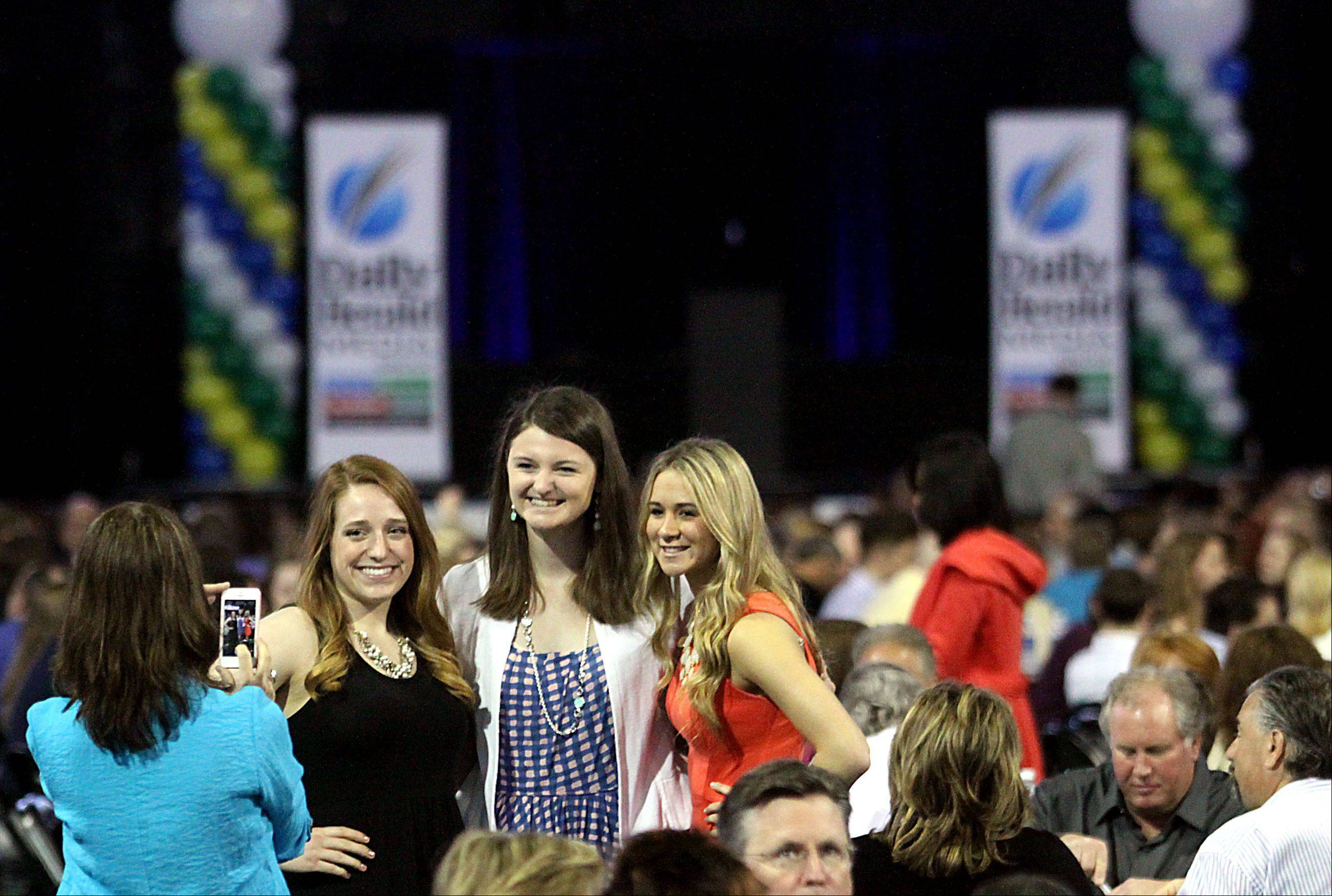 Athletes, from left, Olivia Jakubicek of Cary-Grove High School, Meri Bennett-Swanson of Vernon Hills High School, and Ashley McConnell of Fremd High School pose for pictures during the Daily Herald Prep Sports Excellence event at Sears Centre Arena in Hoffman Estates on Sunday.