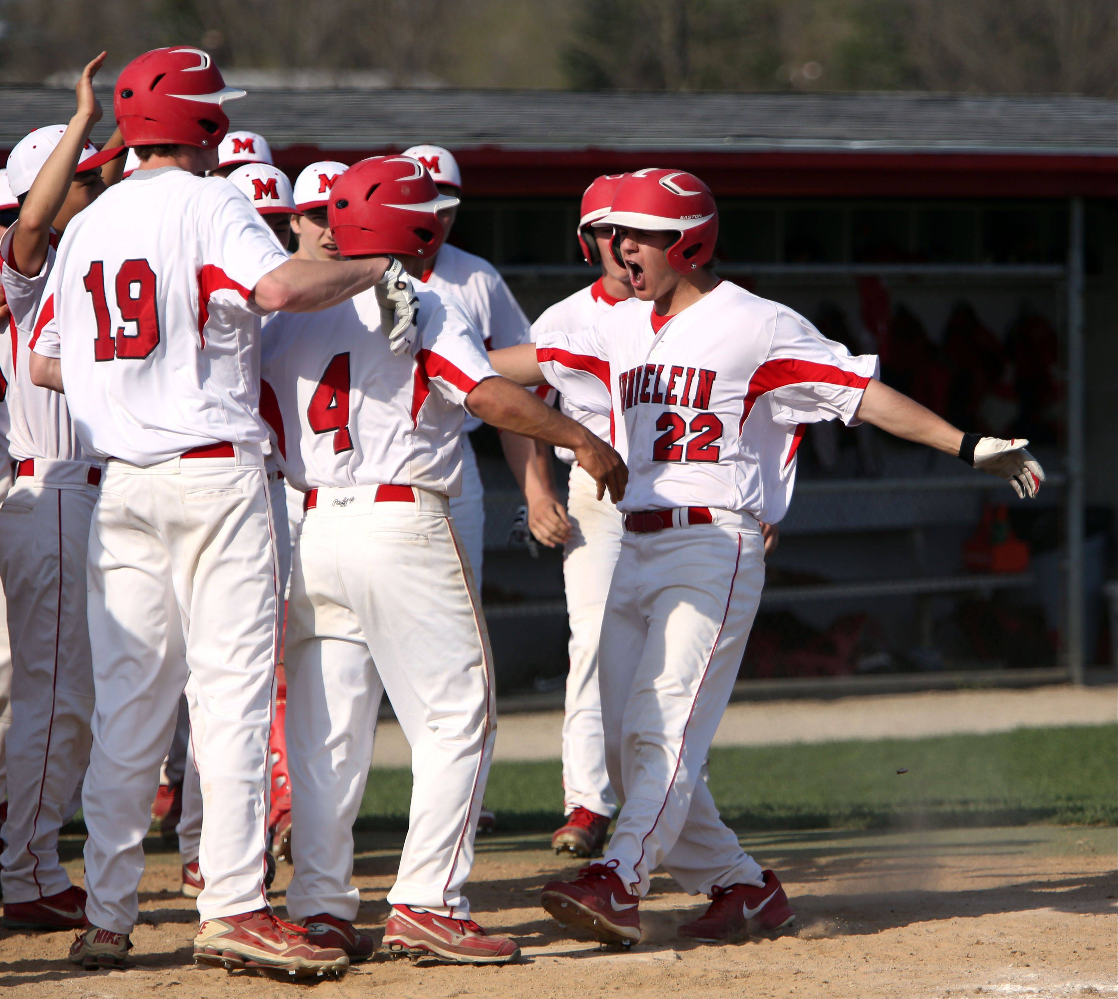 Mundelein�s Will Farmer, right, is met by his teammates as he crosses the plate after a home run against Libertyville on Tuesday at Mundelein.
