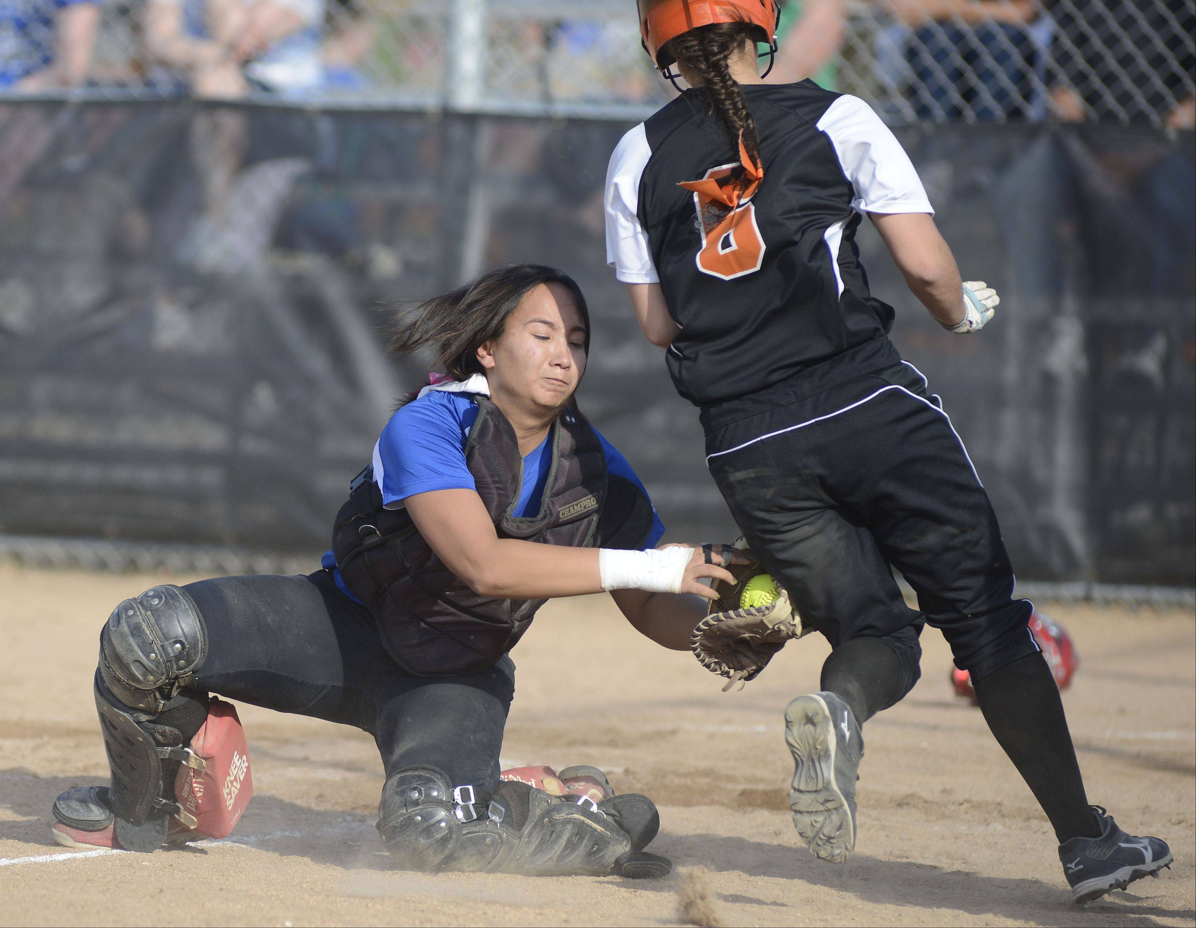 St. Charles East�s Olivia Cheatham is tagged out at home plate by Geneva catcher Kelly Gordon in the fourth inning on Tuesday, April 30.
