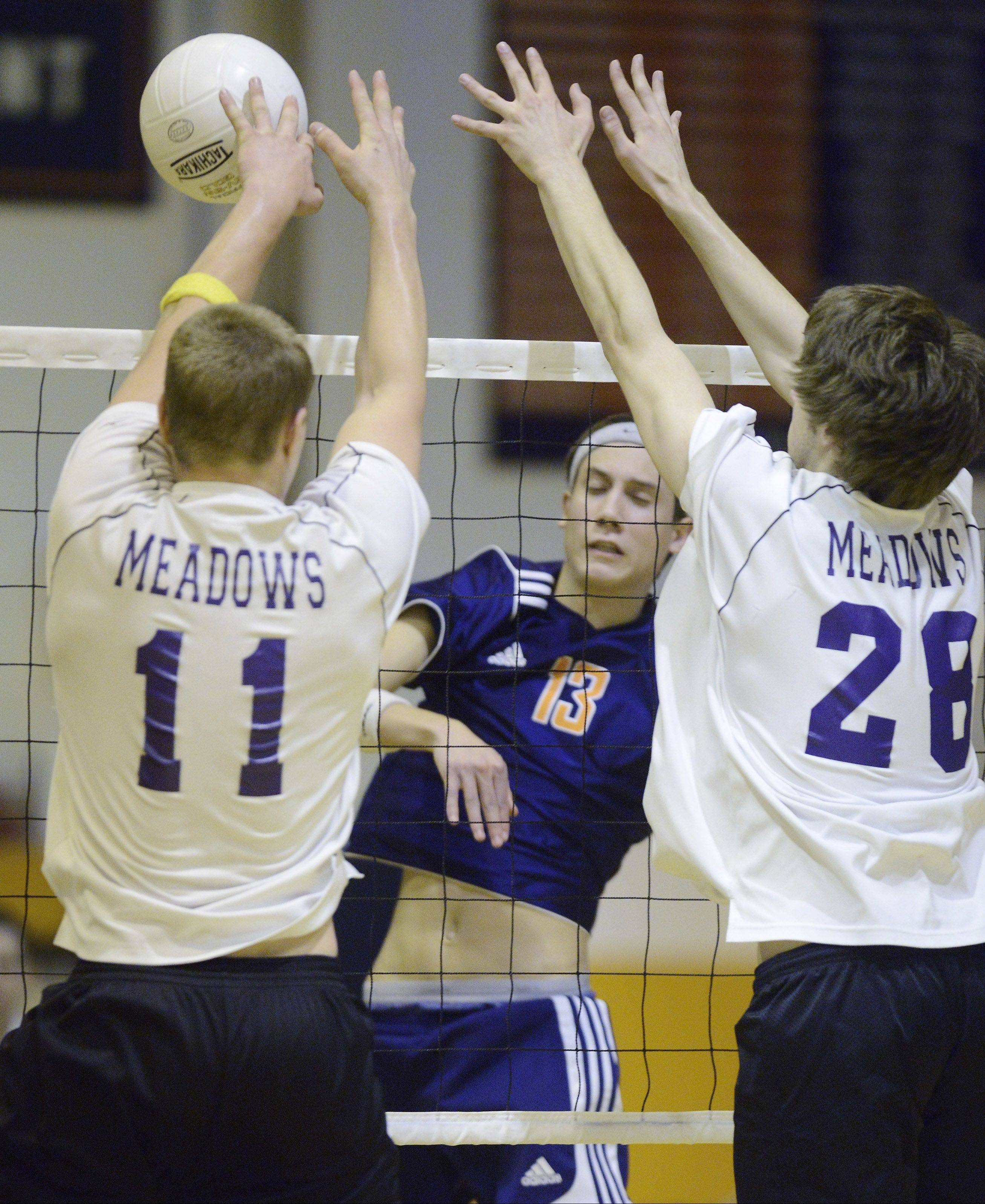 Rolling Meadows� David Sobkowicz, left, and Tom Srnak, right, block a kill attempt by Buffalo Grove�s Athan Cruz during Tuesday�s match at Buffalo Grove.
