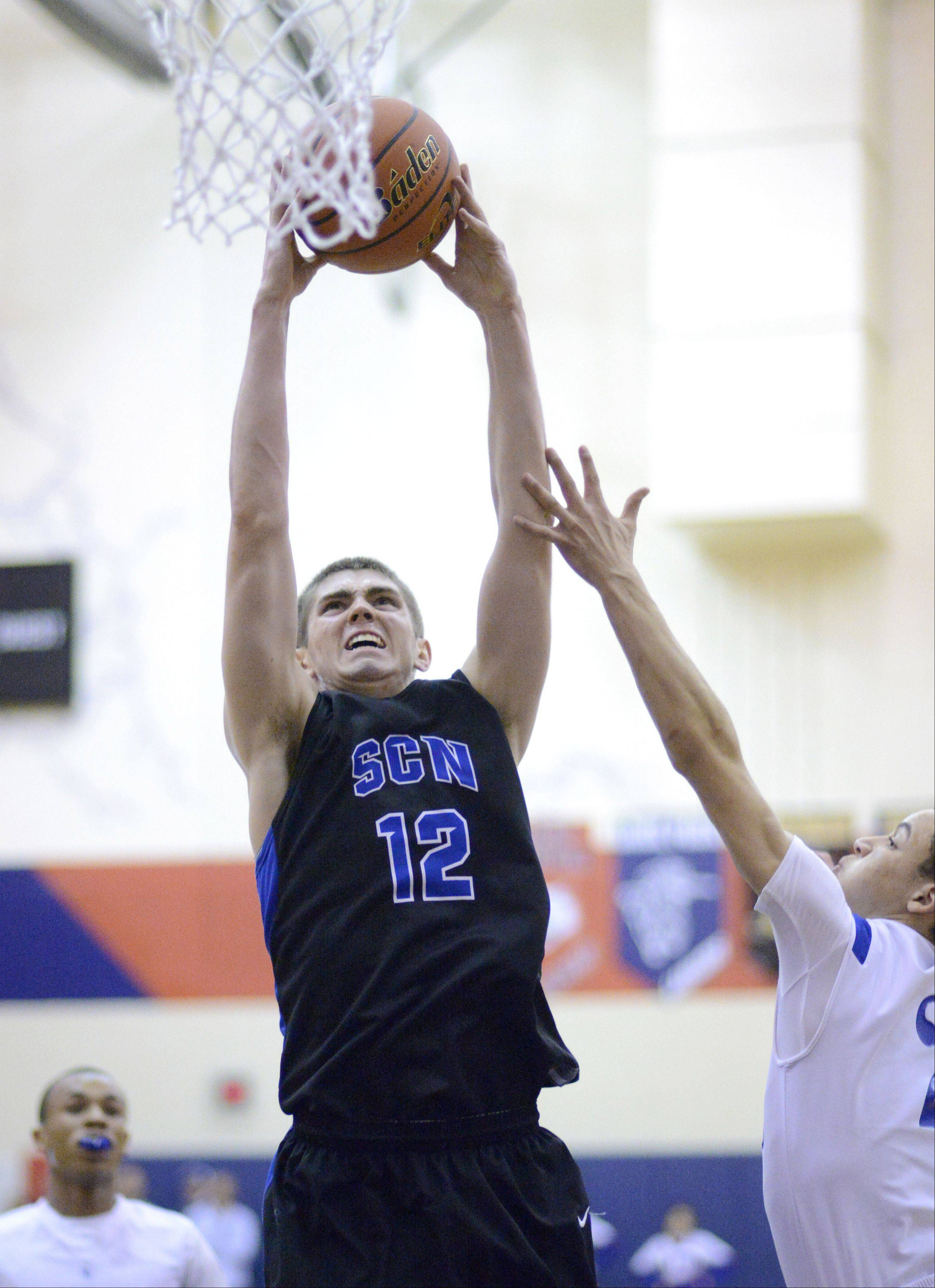 St. Charles North�s Quinten Payne dunks a shot over Larkin�s Derrick Streety this past season. Payne announced Tuesday he will attend Ball State to play his college basketball.