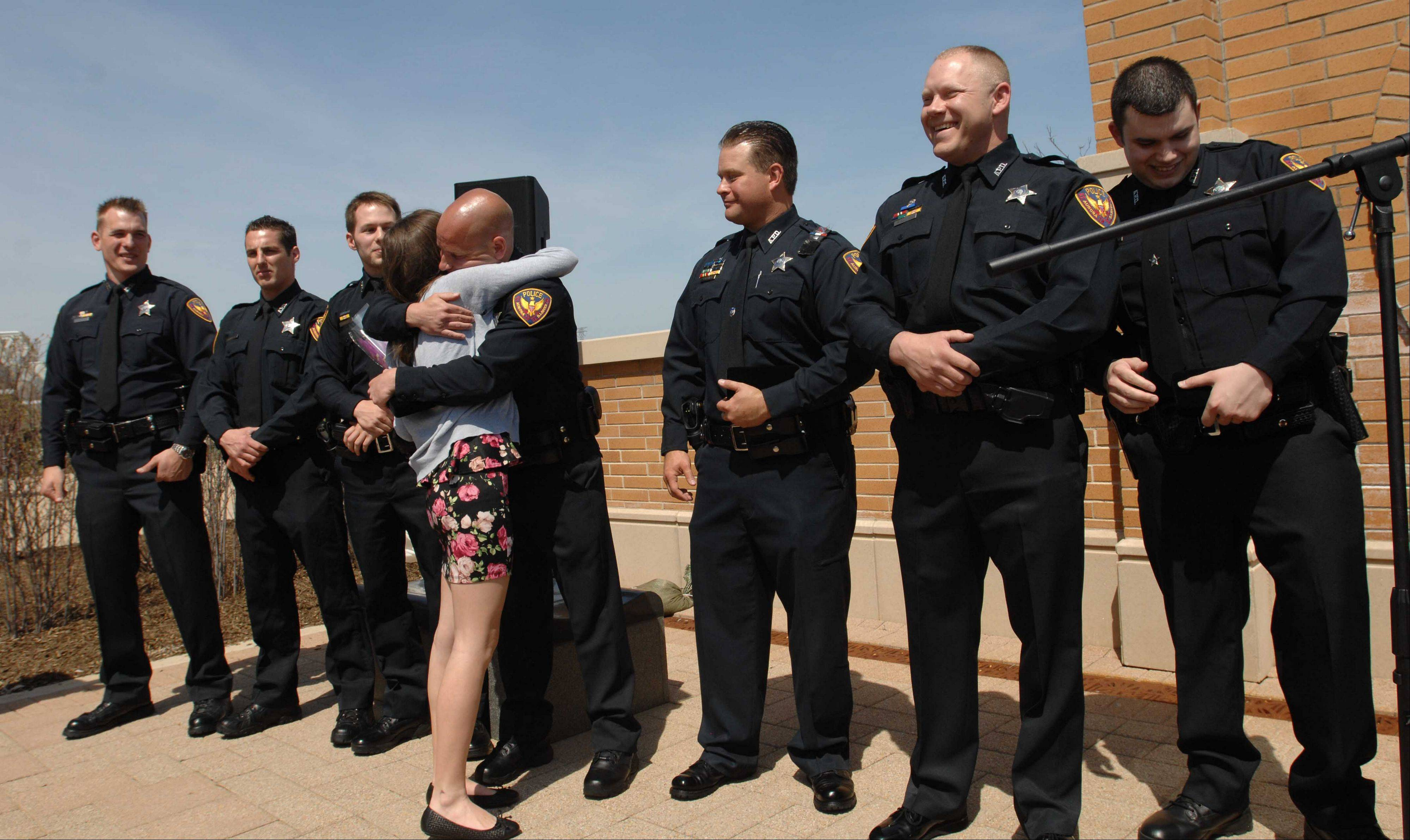 Aurora police investigators Edwin Doepel, Erik Swastek, Greg Christoffel, Jeffrey Hahn, Nicholas Gartner, Joshua Sullivan and officer Chris Coronado wait for a hug from 14-year-old Annie Prosser of Batavia as they are recognized Tuesday afternoon with the Medal of Valor for helping rescue Annie from a car submerged in a pond.