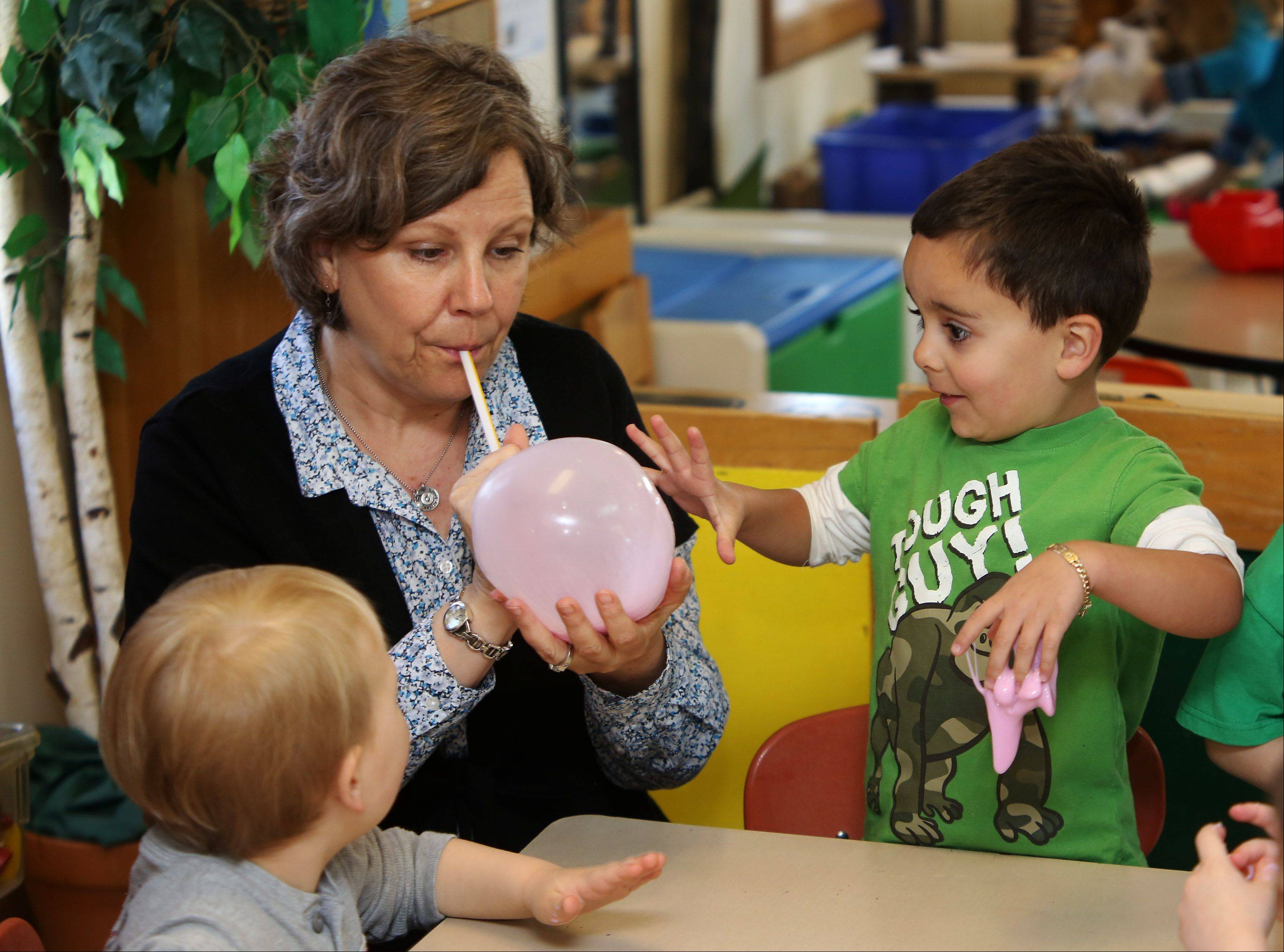 "Teacher Laura Davenport blows a bubble into ""flubber"" under the watchful eye of Christian Caderon, 4, right, as teachers and parents work with children in the one-room class at Mundelein Cooperative Preschool."