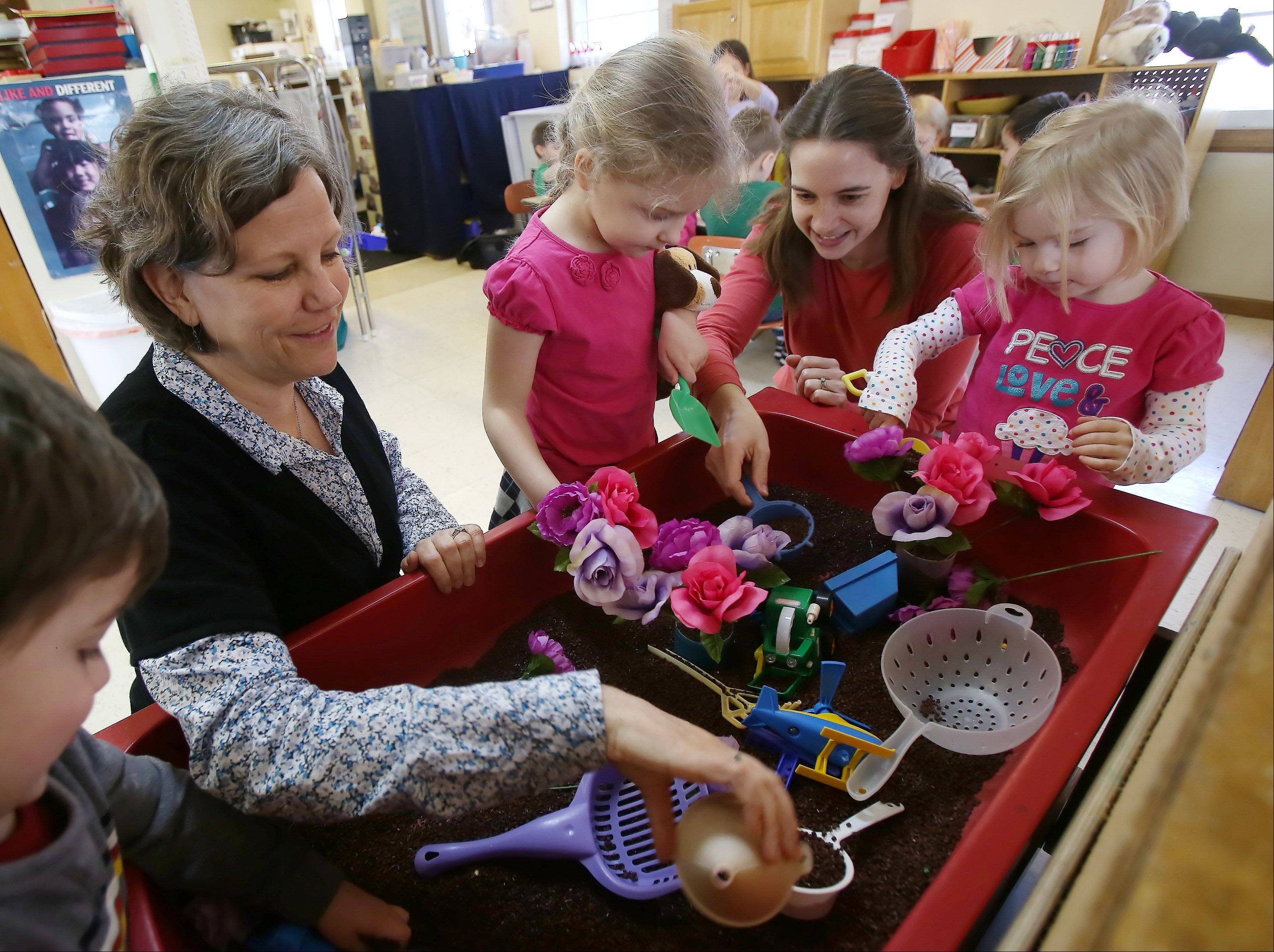 Teacher Laura Davenport, left, plays with Nadia Garrelts, 4, her mother, Erica, and Kayleigh Curran, 4, working to make spring flowers as teachers and parents work with children in the one-room class at Mundelein Cooperative Preschool.