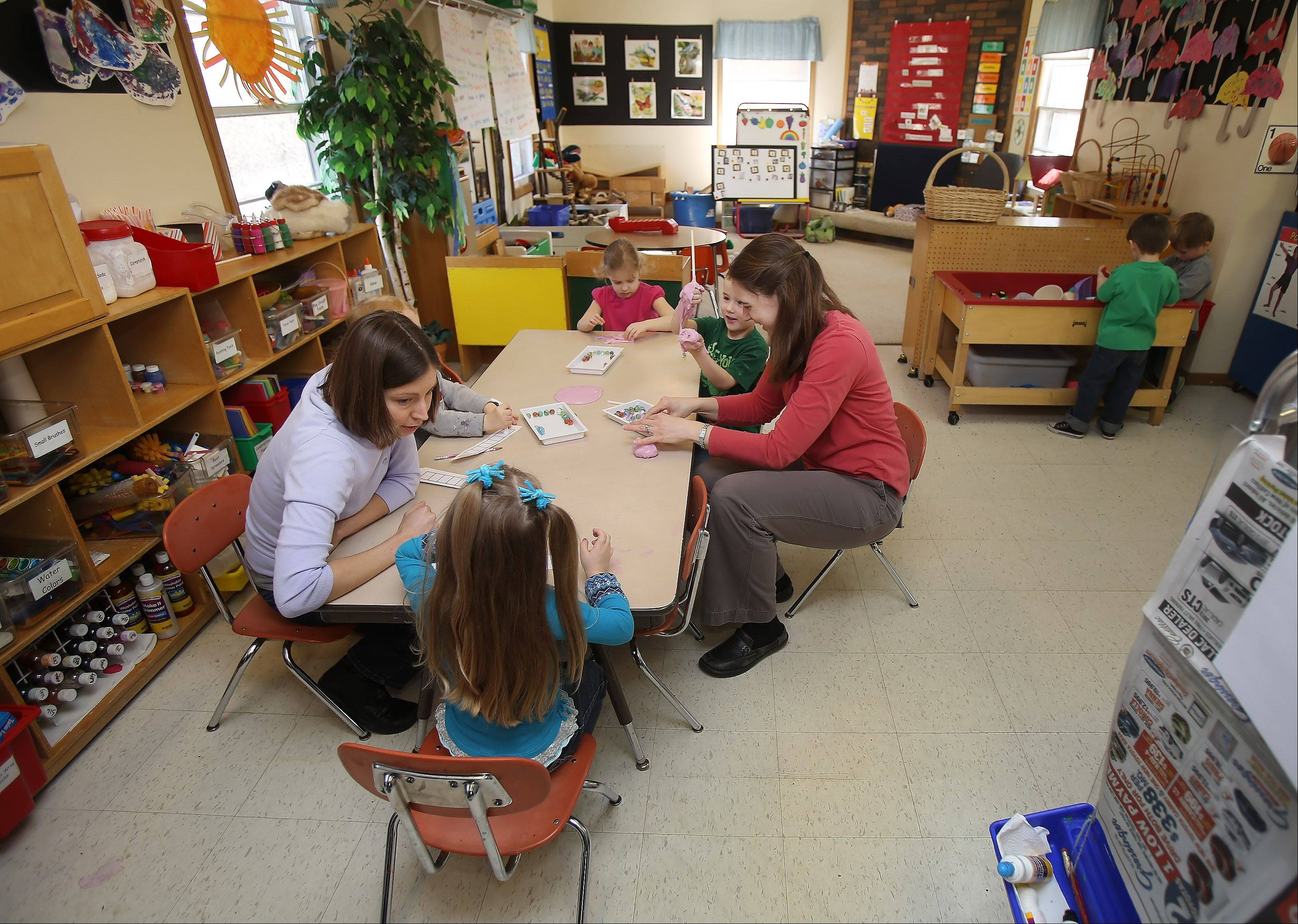 Assistant teacher Reagan Baiter, left, and mother Erica Garrelts work with children in a one-room class at Mundelein Cooperative Preschool.