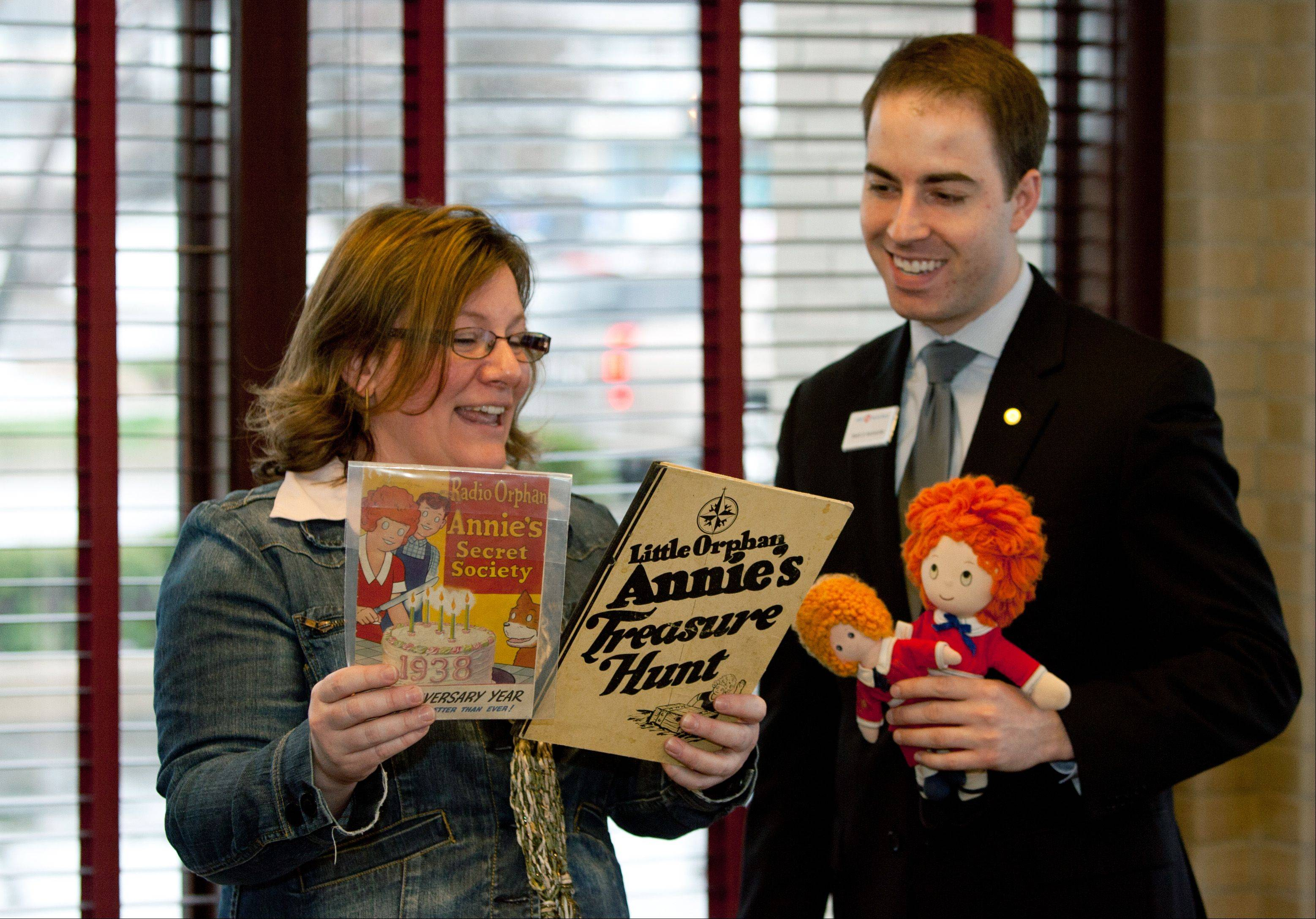 Mark Bennecke, bank manager of BMO Harris Bank in downtown Lombard, donates a collection of Little Orphan Annie items to Jeanne Schultz Angel, executive director of the Lombard Historical Society. The historical society will display the memorabilia honoring the creation of Lombard cartoonist Harold Gray in a new exhibit to be designed with a $45,000 state grant.