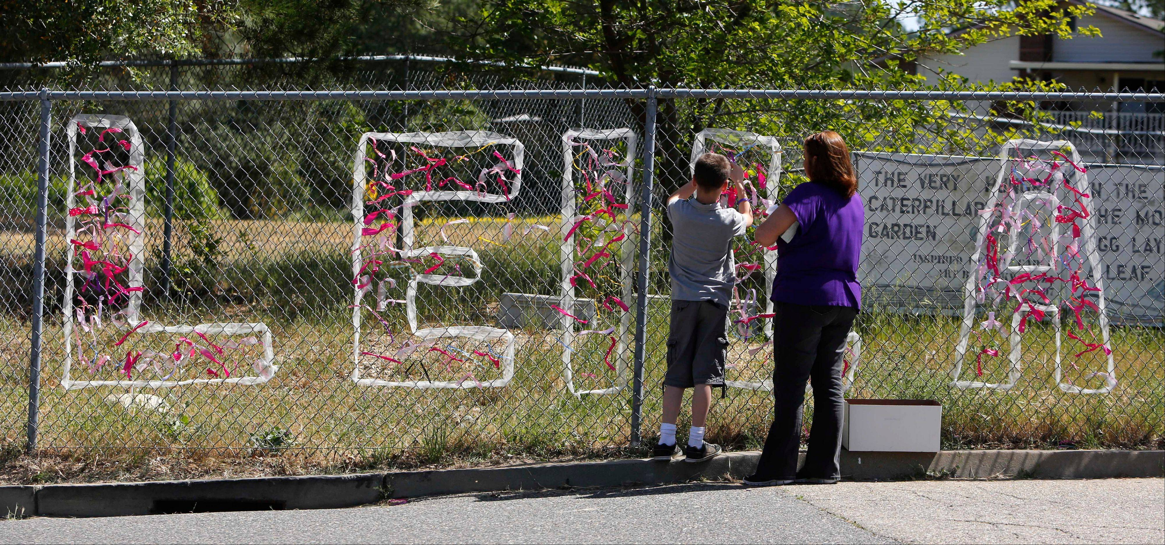 Teacher Cecilia Richardson helps a student tie a ribbon honoring murder victim, third-grader Leila Fowler, at Jenny Lind Elementary School in Valley Springs, Calif., Monday April 29, 2013. Authorities are searching for the killer of Fowler, 8, who was found by her 12-year-old brother in the family's Valley Springs home Saturday.