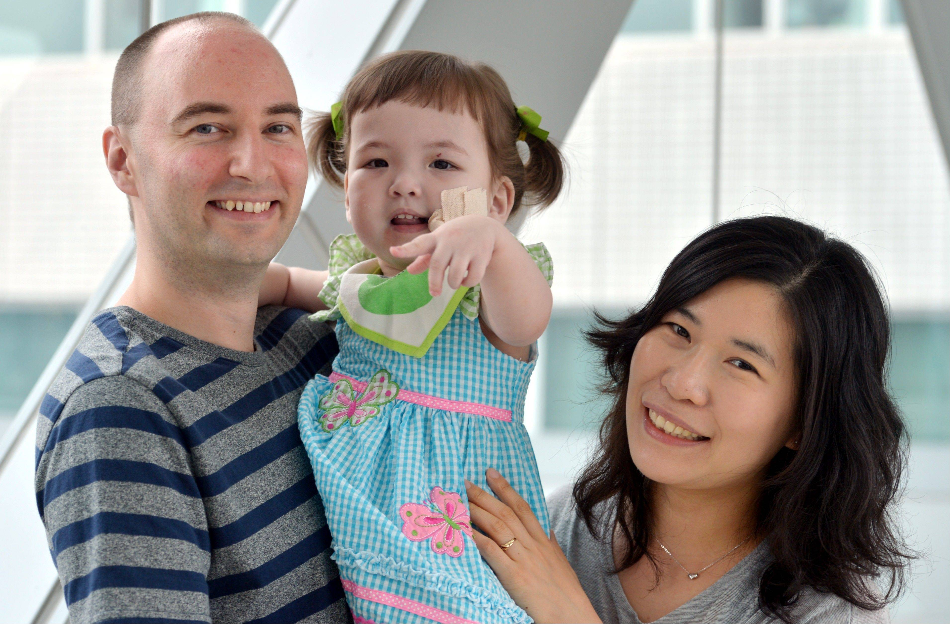 In this 2012 photo, Hannah Warren, 2, poses with her parents Lee Young-mi and Darryl Warren at Seoul National University Hospital in Seoul, South Korea. Hannah received a new windpipe made from her own stem cells in a landmark operation on April 9 at Children's Hospital of Illinois in Peoria.