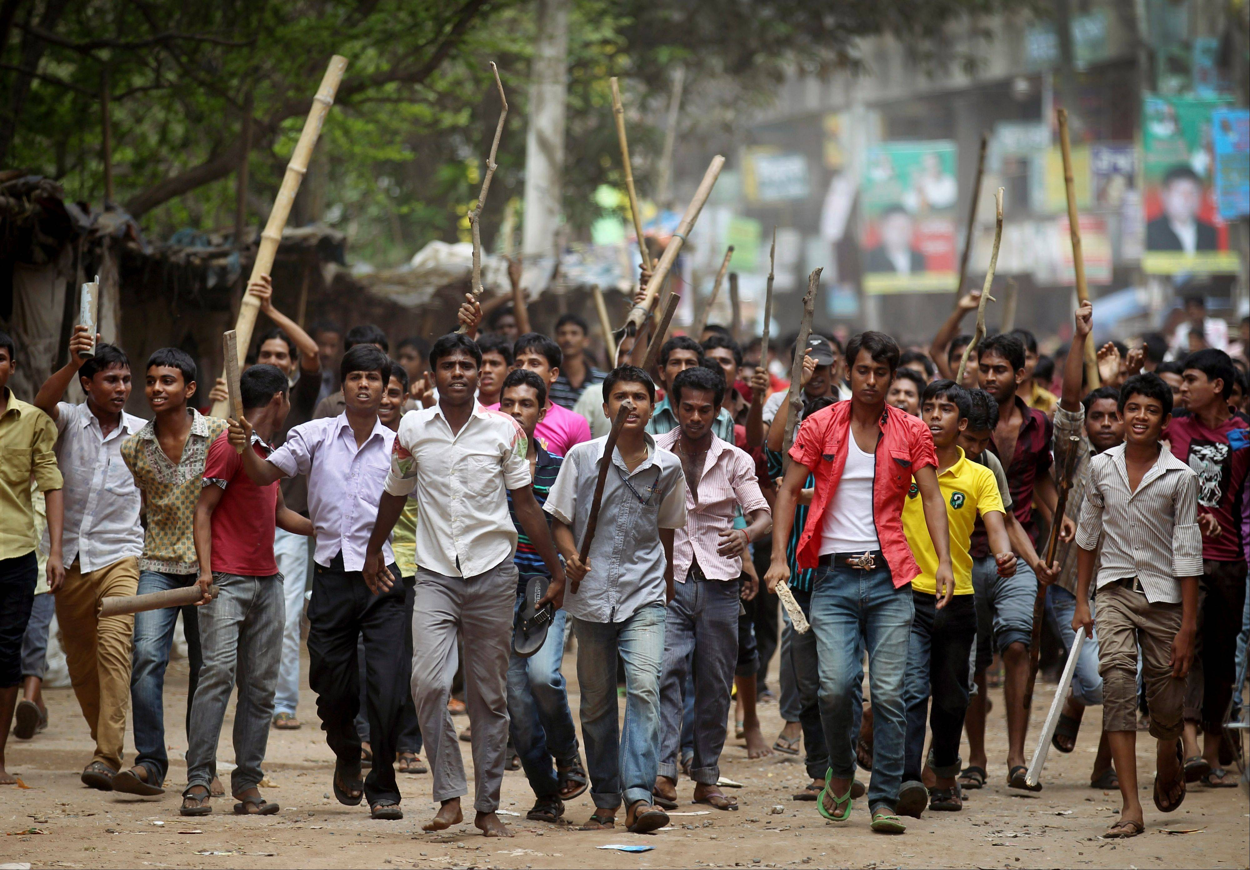 "Protesters march down a street demanding the death penalty for those responsible for the collapsed garment factory building, killing hundreds, Tuesday, April 30, 2013 in Savar, near Dhaka, Bangladesh. A top Bangladesh court on Tuesday ordered the government to ""immediately"" confiscate the property of a collapsed building's owner, as thousands of protesters demanding death penalty for the man clashed with police, leaving 100 people injured."