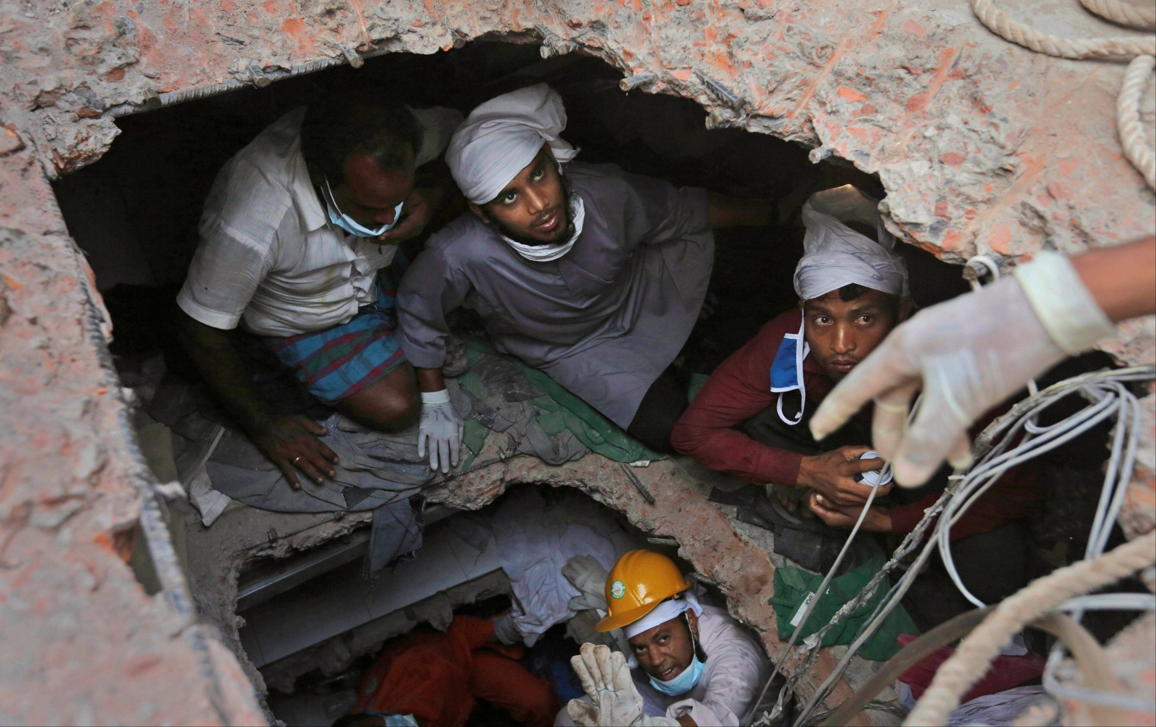 Bangladeshi rescue workers search for survivors as they are seen through a hole in the roof a building that collapsed Wednesday. Hundreds of volunteers rushed to the site of a building that collapsed last week to rescue thousands of people trapped in the rubble. They were ordinary folk -- self-taught medics and neophyte rescuers.