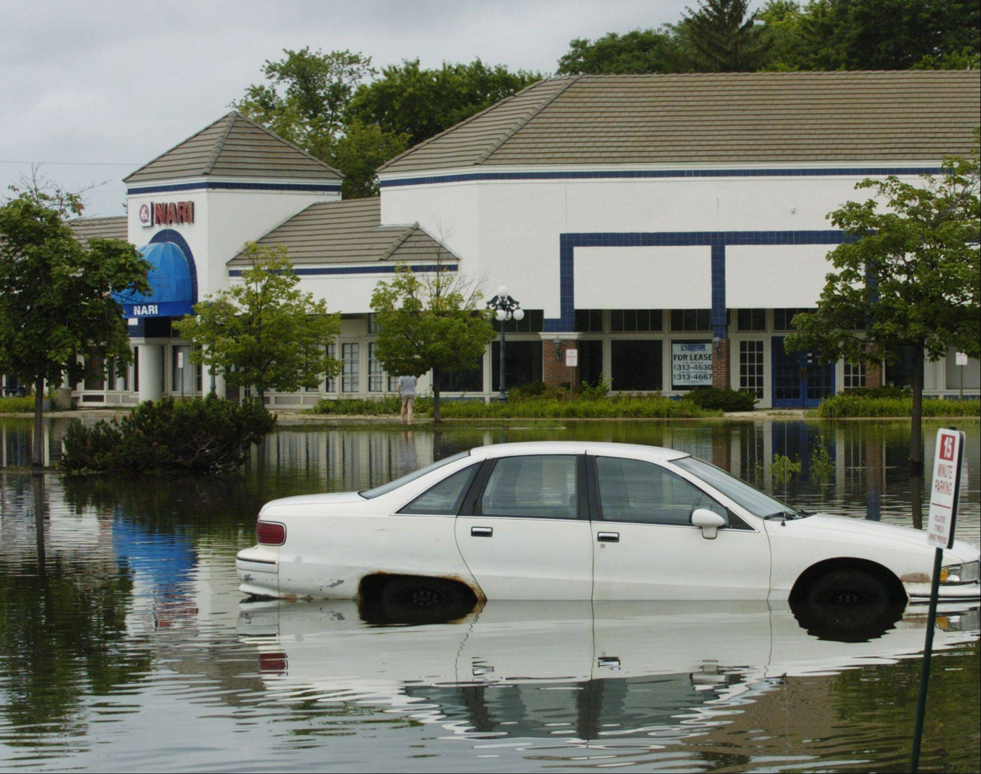 A car sits in floodwater in the International Plaza parking lot on Golf Road just east of Arlington Heights Road after heavy rain in July 2011 in Arlington Heights. The village has two studies under way to address flooding from that storm.