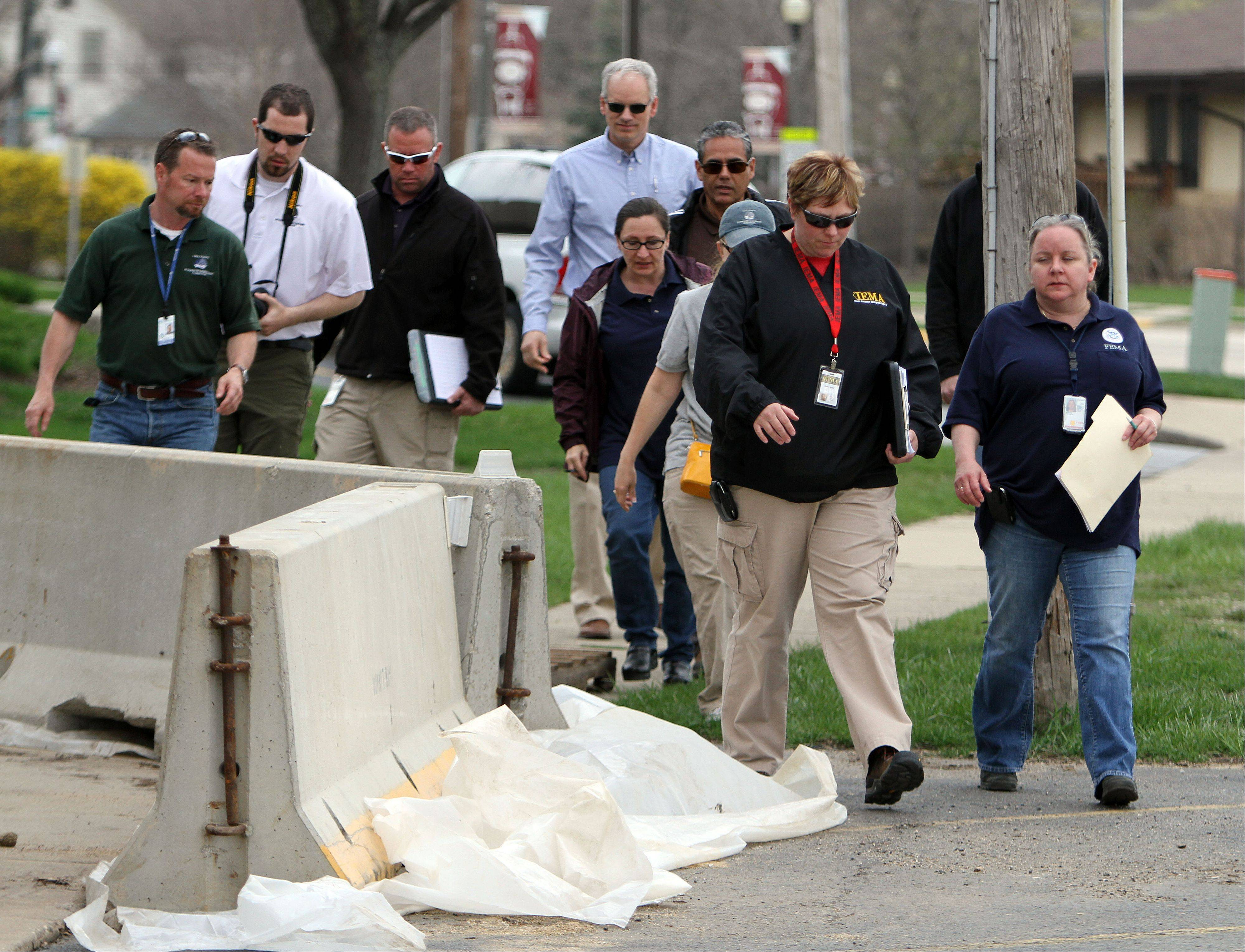 Members of the Federal Emergency Management Agency, Illinois Emergency Managemant Agency, Lake County Stormwater Management Commission and the Small Business Administration walk through flood-damaged areas off Old Grand Avenue in Gurnee on Monday.