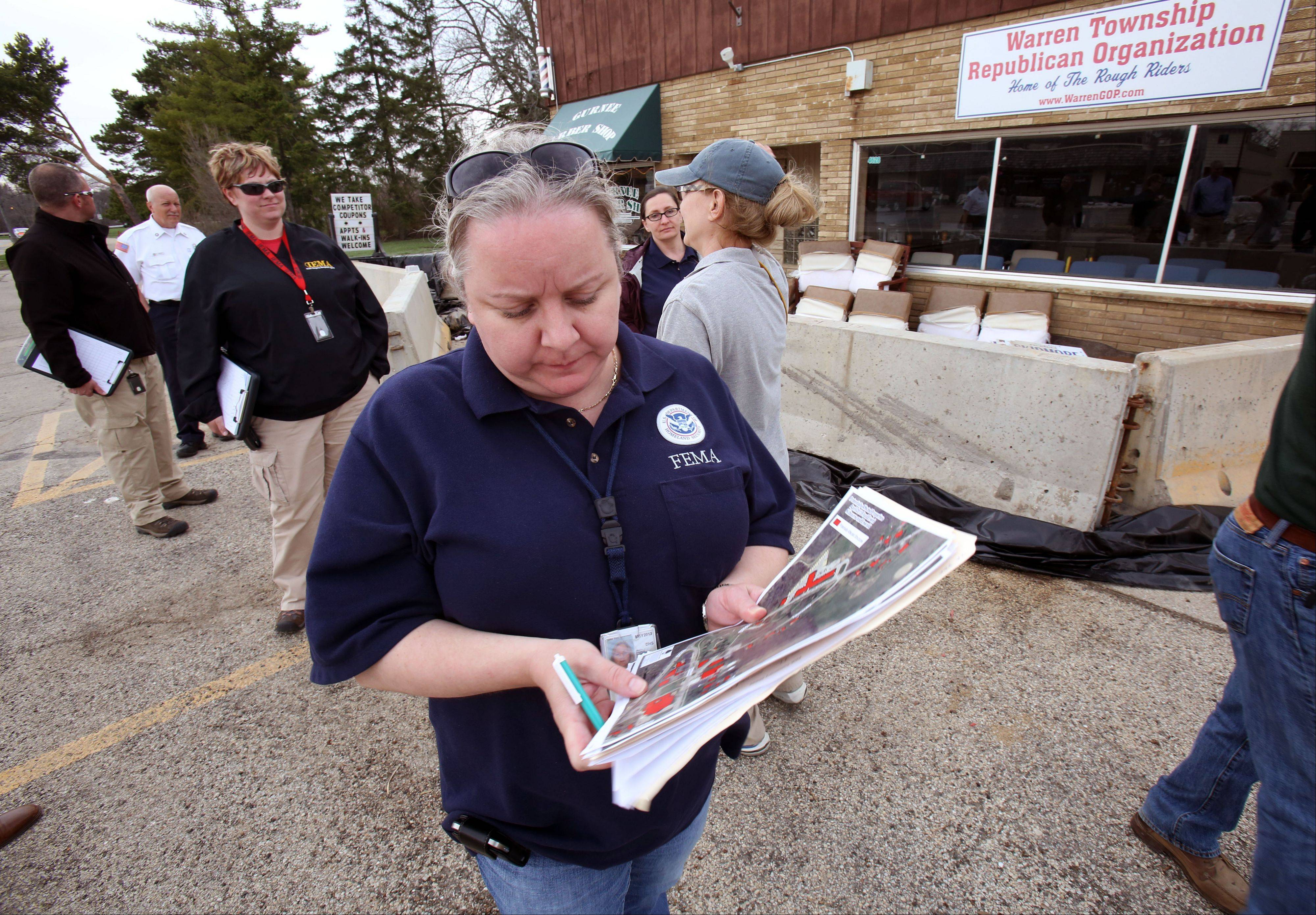 Suzanne Vermeer with the Federal Emergency Management Agency takes notes Monday as she checks out flood damage in Gurnee.