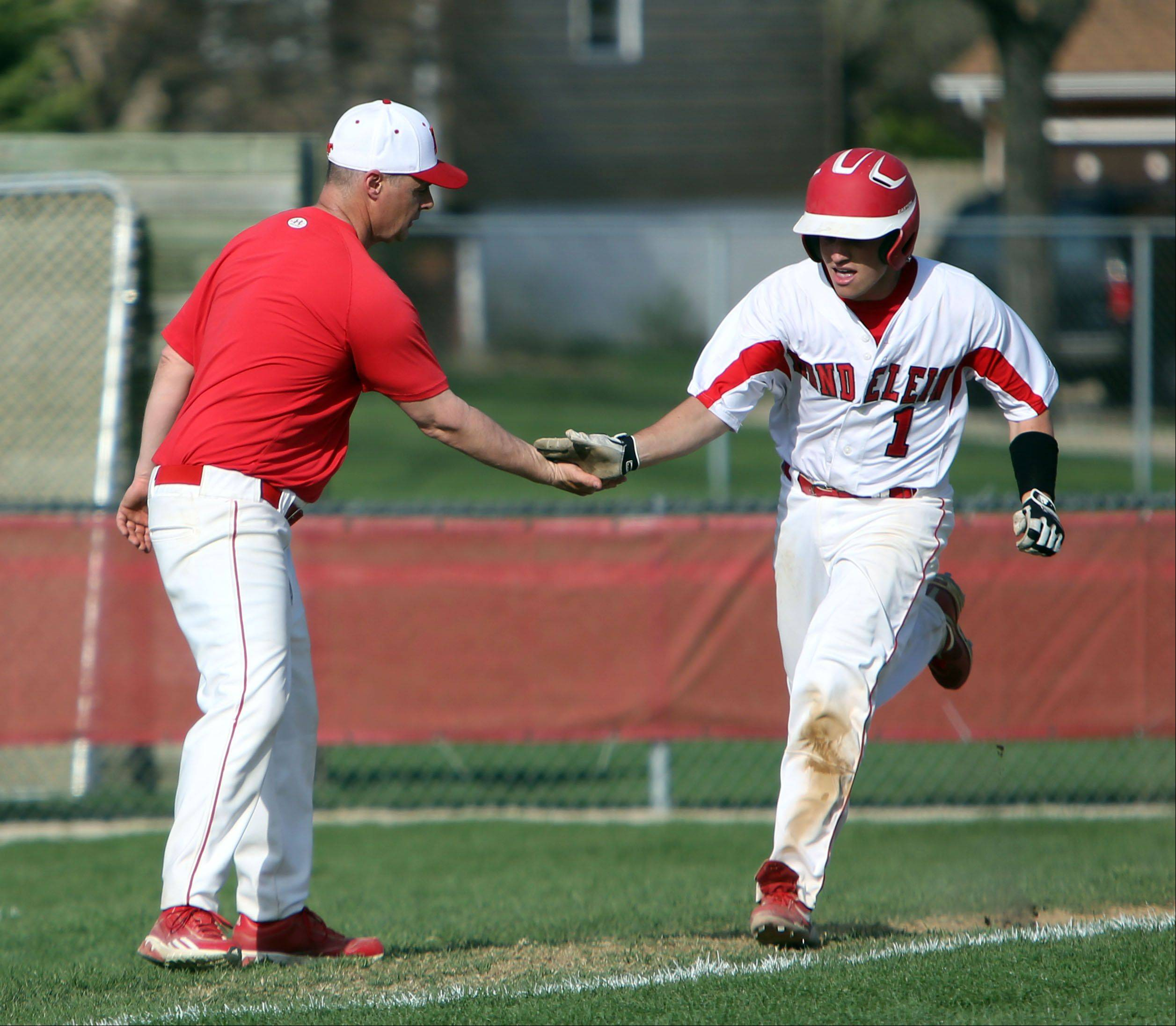 Mundelein coach Todd Parola, left, congratulates Logan Reckert as he rounds third base after a home run during their game against Libertyville Tuesday at Mundelein High School.
