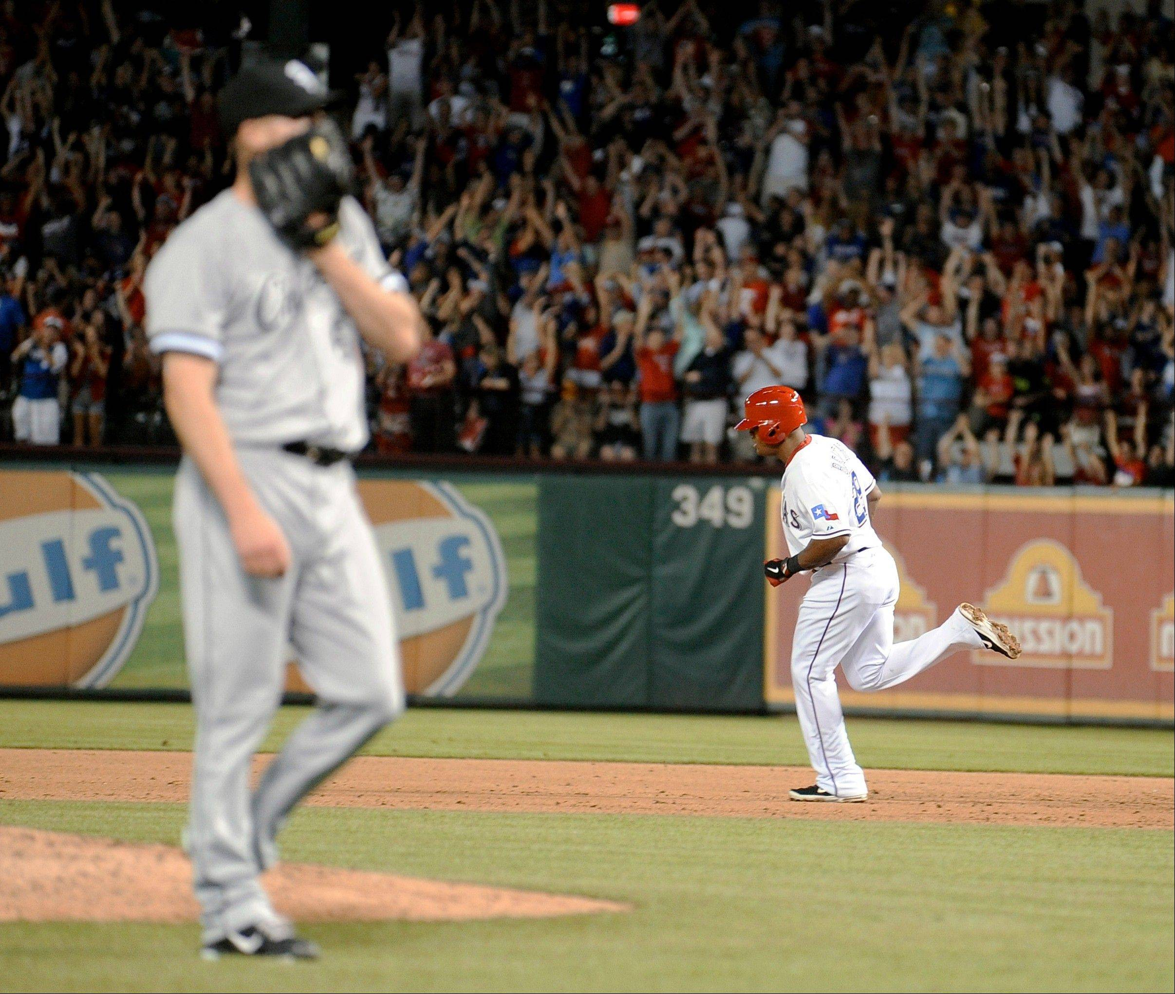 The Rangers' Adrian Beltre rounds the bases as Chicago White Sox relief pitcher Nate Jones reacts to giving up a two-run home run in the sixth inning Tuesday in Arlington, Texas.