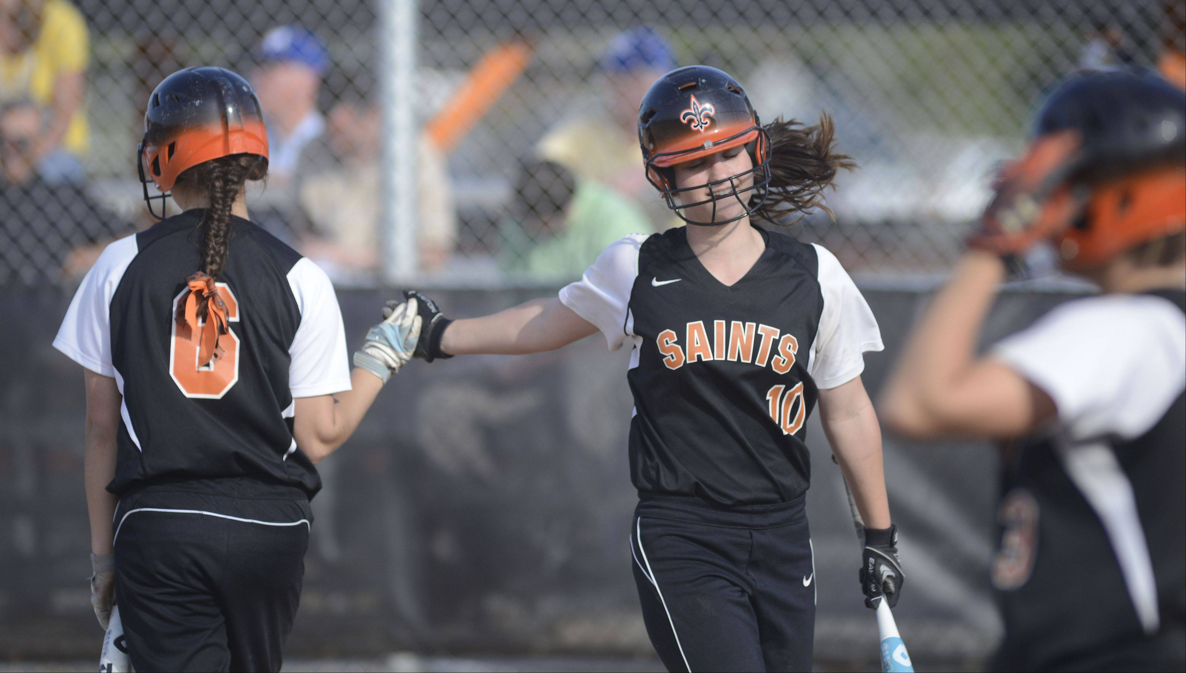St. Charles East's Kate Peterburs (10) gets congrats after scoring a run in the fourth inning from teammate Olivia Cheatham on Tuesday, April 30.