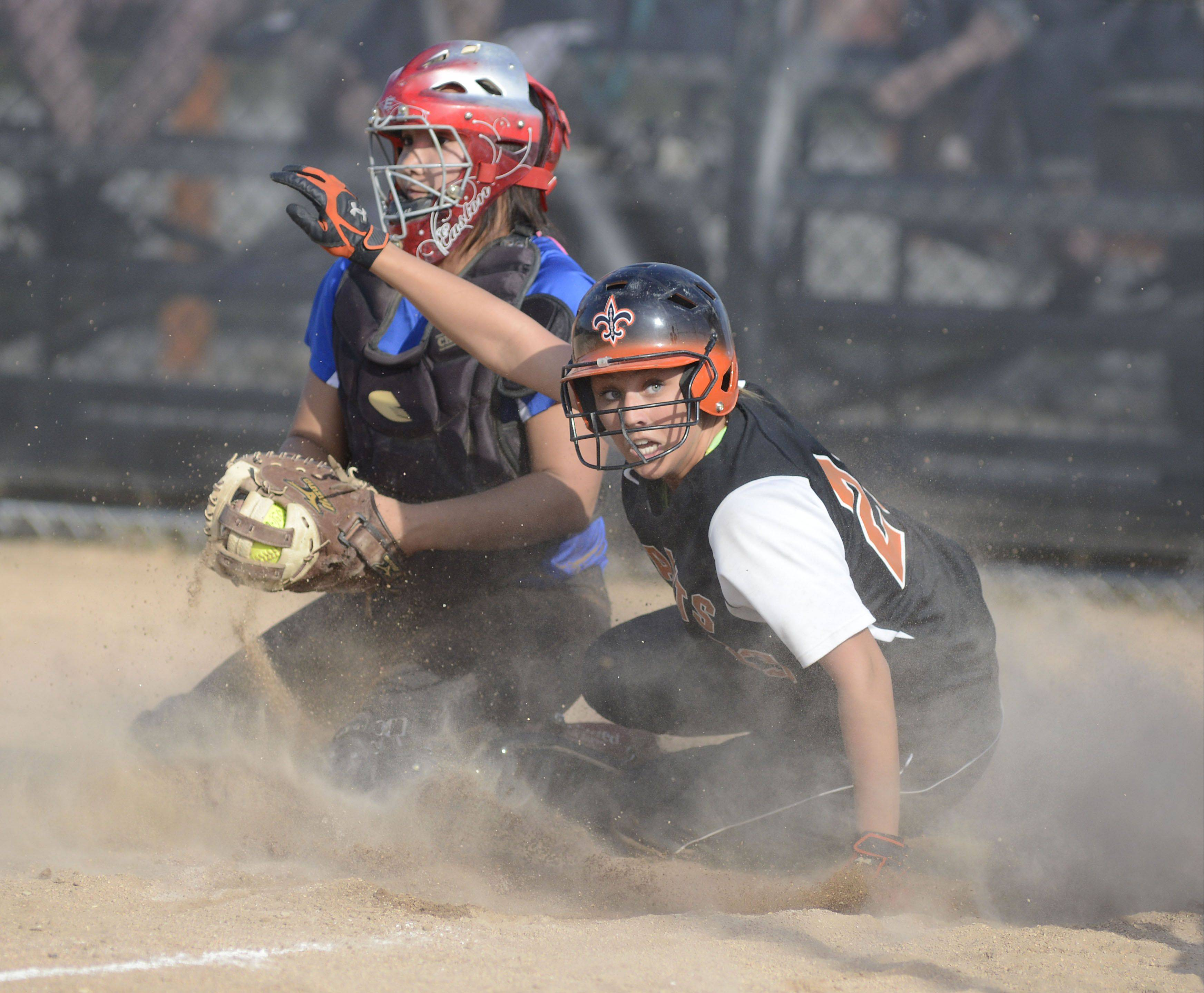 St. Charles East's Mackenzie Meadows is safe on home plate from Geneva's Kelly Gordon in the fourth inning on Tuesday, April 30.