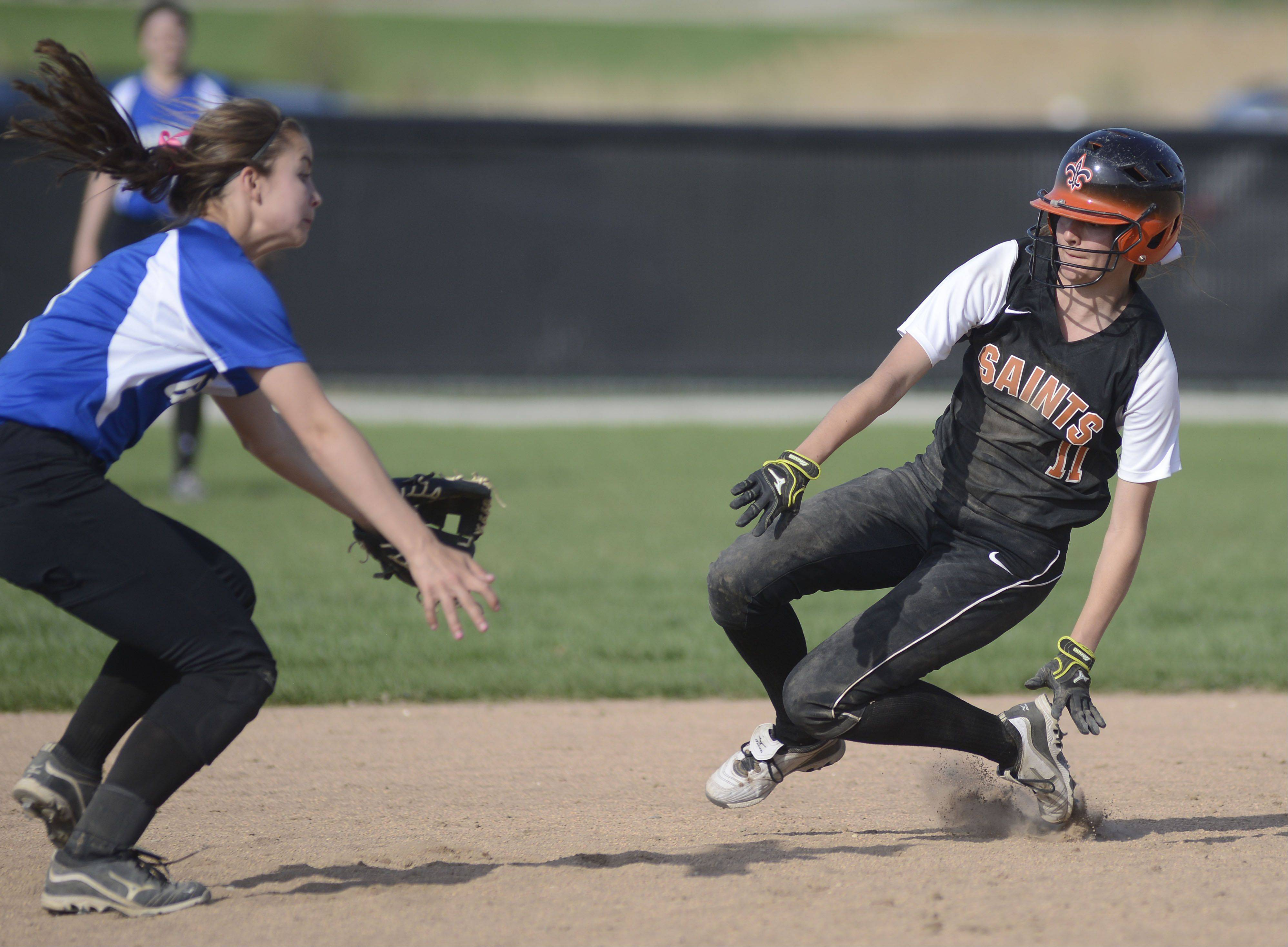 St. Charles East's Tess Hupe is safe on second base before the ball just misses the glove of Geneva's Anna Geary in the third inning on Tuesday, April 30.
