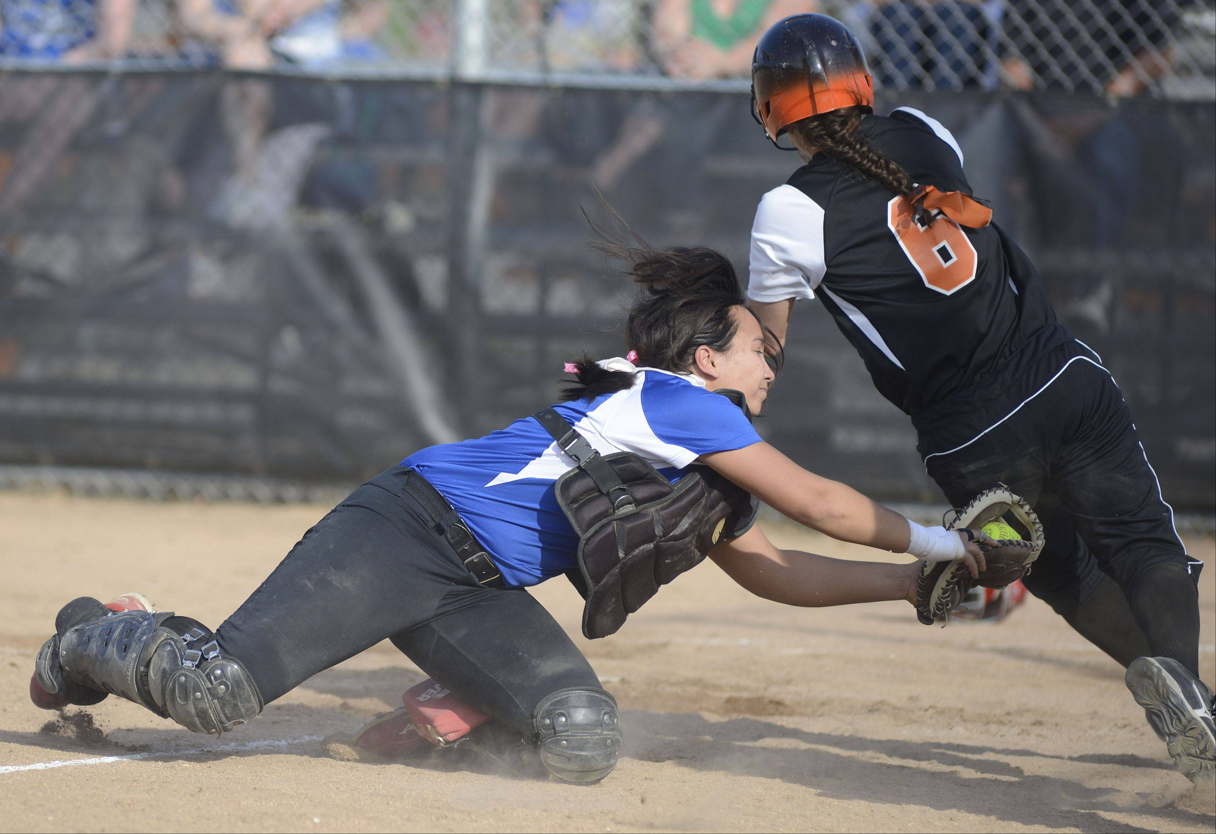 St. Charles East's Olivia Cheatham is tagged out at home plate by Geneva catcher Kelly Gordon in the fourth inning on Tuesday, April 30.