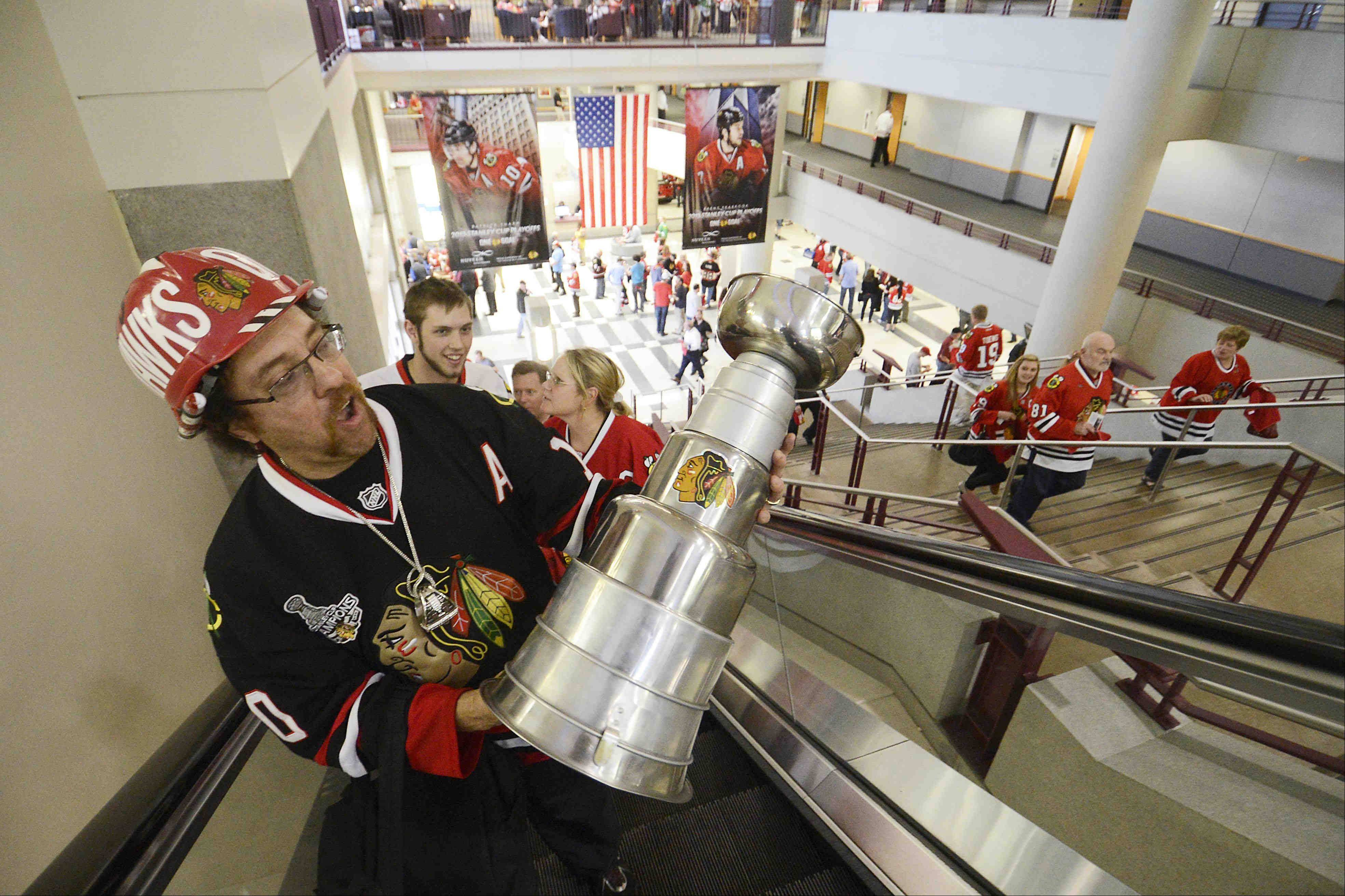 Ray Alcala Jr. of Lockport, carries his homemade Stanley Cup up the escalator. He made the trophy out of kitchen pots and dog dishes during the 2010 season.