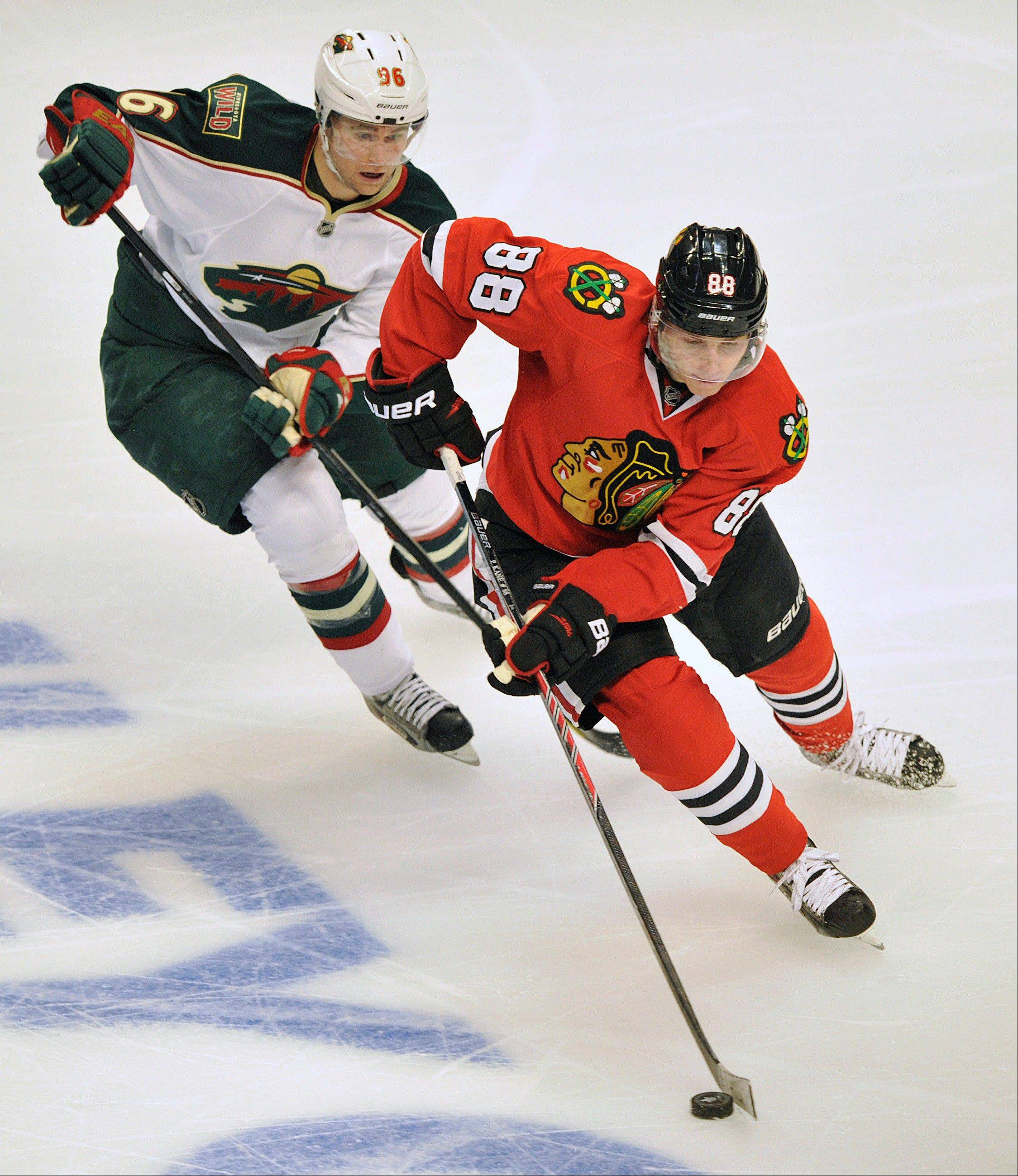 Minnesota Wild's Pierre-Marc Bouchard, left, and Chicago Blackhawks' Patrick Kane (88) race for the puck during the second period of Game 1 of an NHL hockey Stanley Cup playoff series Tuesday, April 30, 2013, in Chicago.
