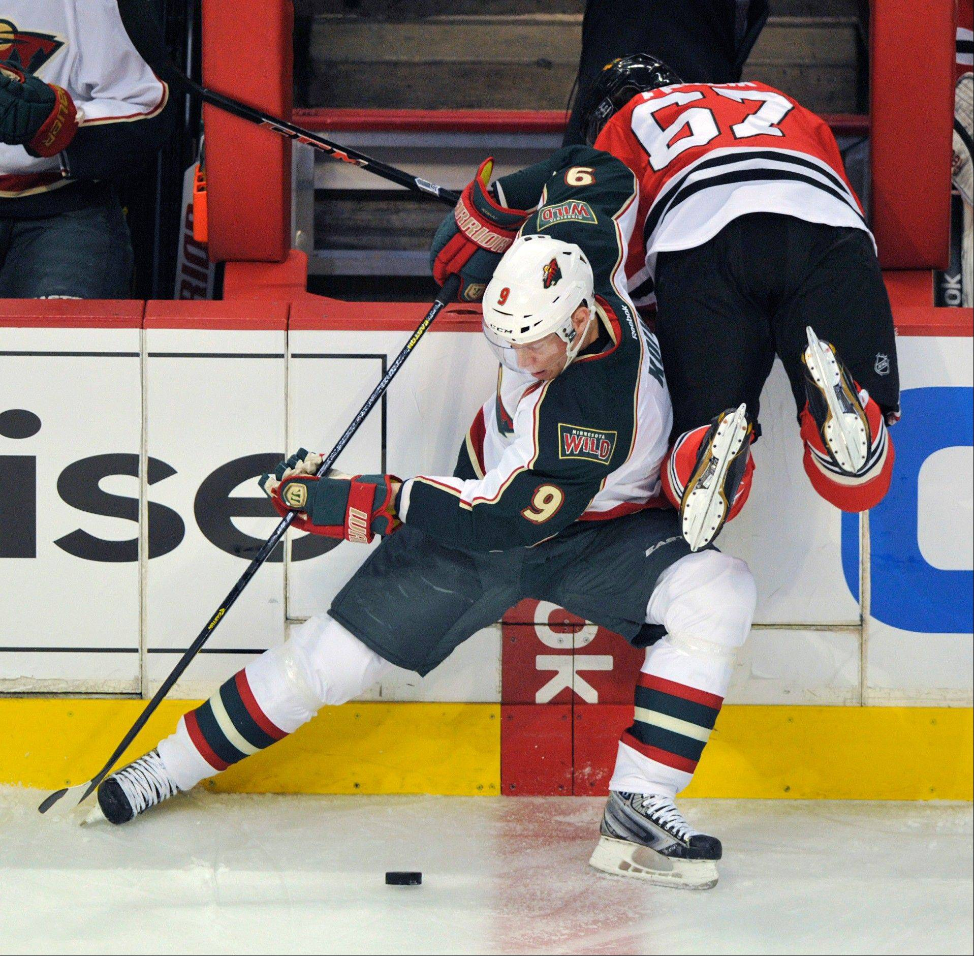 Minnesota Wild's Mikko Koivu (9) tries to control the puck as Chicago Blackhawks' Michael Frolik (67) crashes over the boards during the first period of Game 1 of an NHL hockey Stanley Cup playoff series, Tuesday, April 30, 2013, in Chicago.