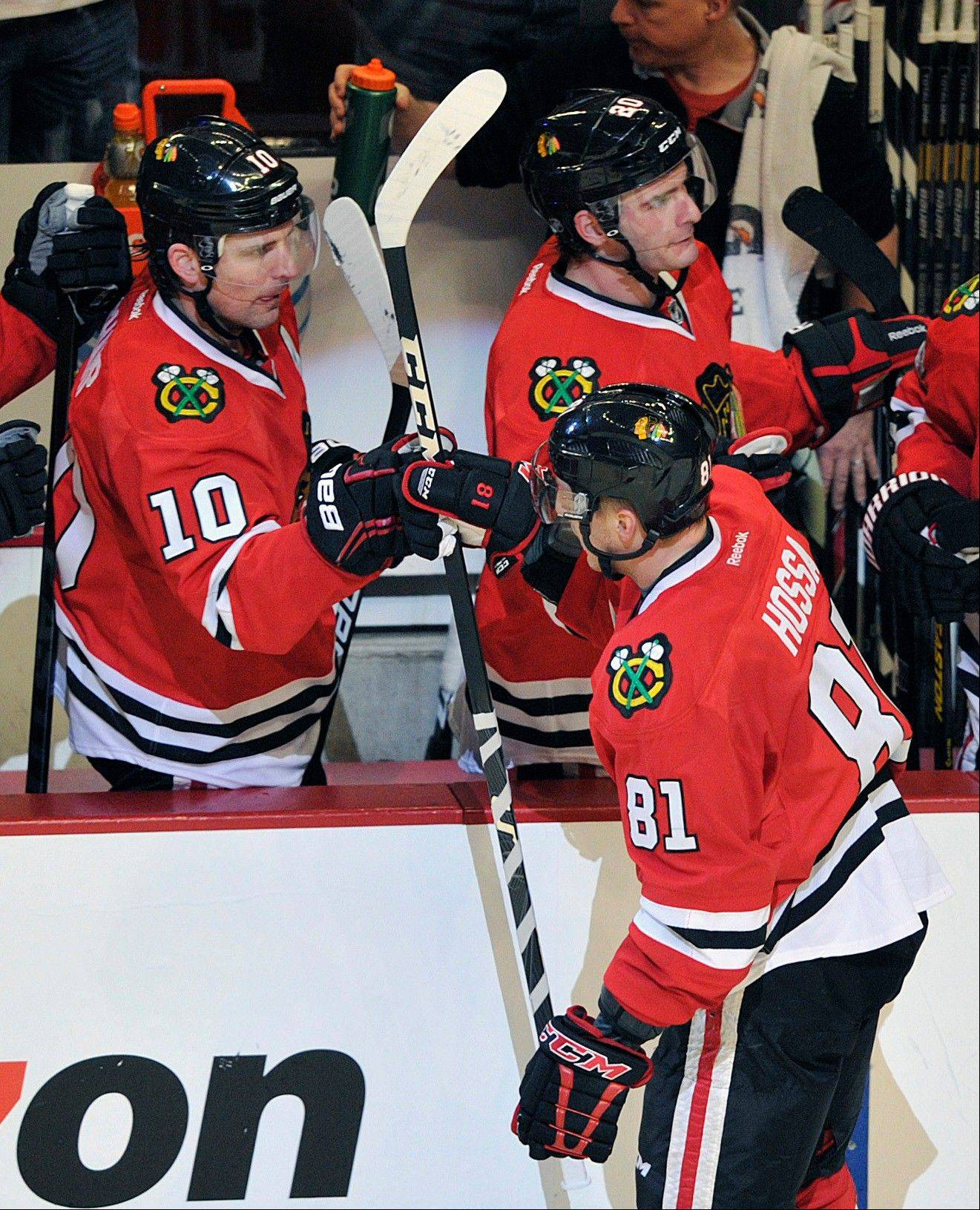 Chicago Blackhawks' Patrick Sharp (10) congratulates Marian Hossa (81) after Hossa's goal against the Minnesota Wild during the second period of Game 1 of an NHL hockey Stanley Cup playoff series Tuesday, April 30, 2013, in Chicago.