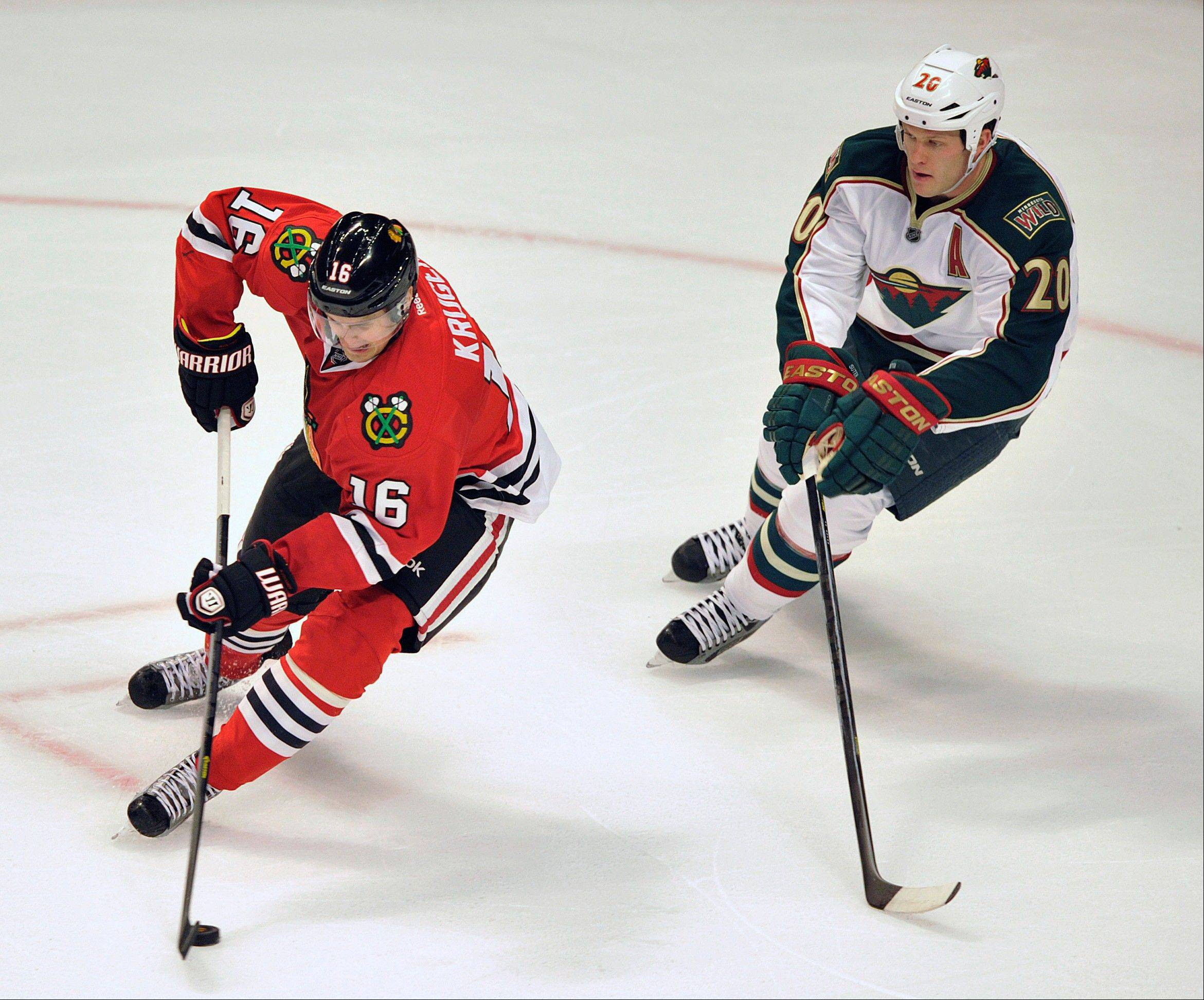Chicago Blackhawks' Marcus Kruger (16) backhands a shot as Minnesota Wild's Ryan Suter defends during the second period of Game 1 of an NHL hockey Stanley Cup playoff series Tuesday, April 30, 2013, in Chicago.