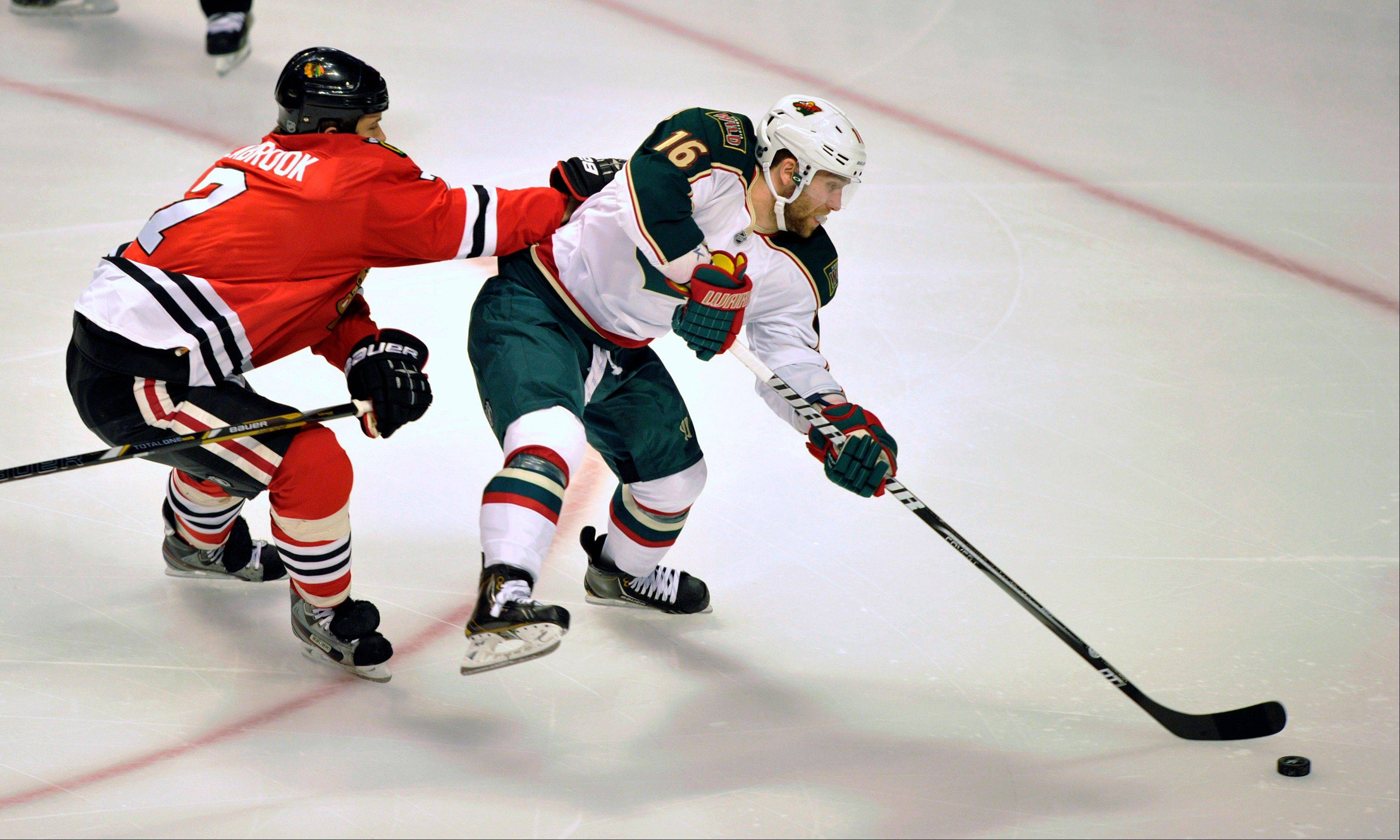 Chicago Blackhawks' Brent Seabrook checks the Minnesota Wild's Jason Zucker (16) as he handles the puck during the first period of Game 1 of an NHL hockey Stanley Cup playoff series, Tuesday, April 30, 2013, in Chicago.
