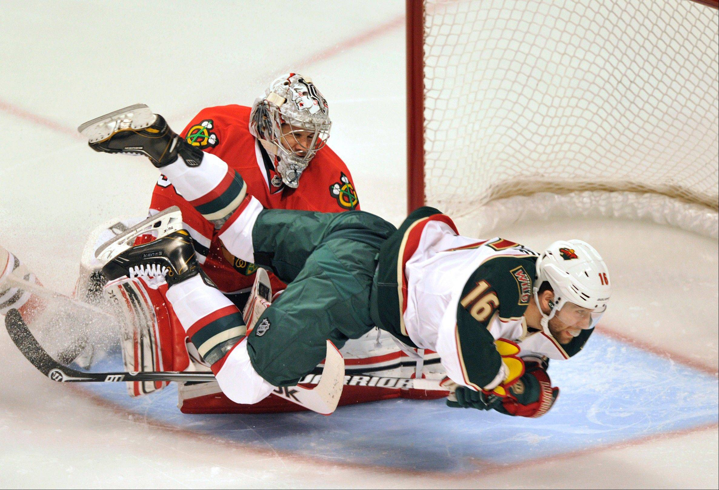 Minnesota Wild's Jason Zucker (16) collides with Chicago Blackhawks' Corey Crawford during the first period of Game 1 of an NHL hockey Stanley Cup playoff series, Tuesday, April 30, 2013, in Chicago.