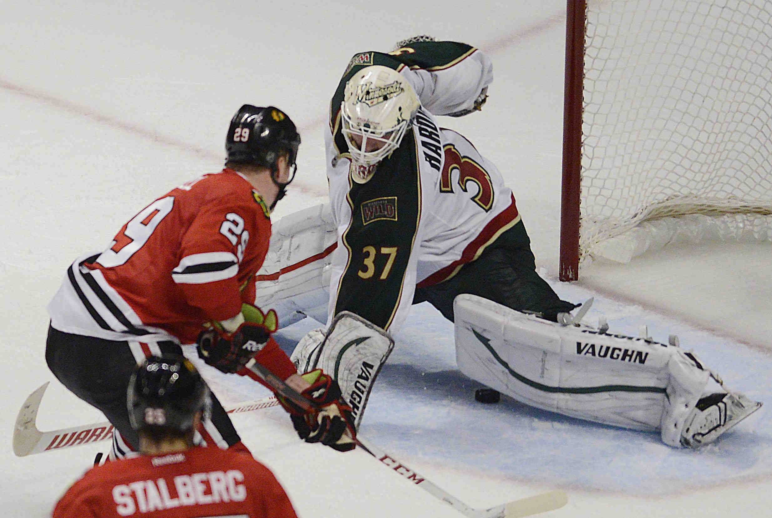 Chicago Blackhawks left wing Bryan Bickell slips the puck under the knee of Minnesota Wild goalie Josh Harding in overtime for the win Tuesday in Game 1 of the Western Conference first-round playoff series at the United Center in Chicago.