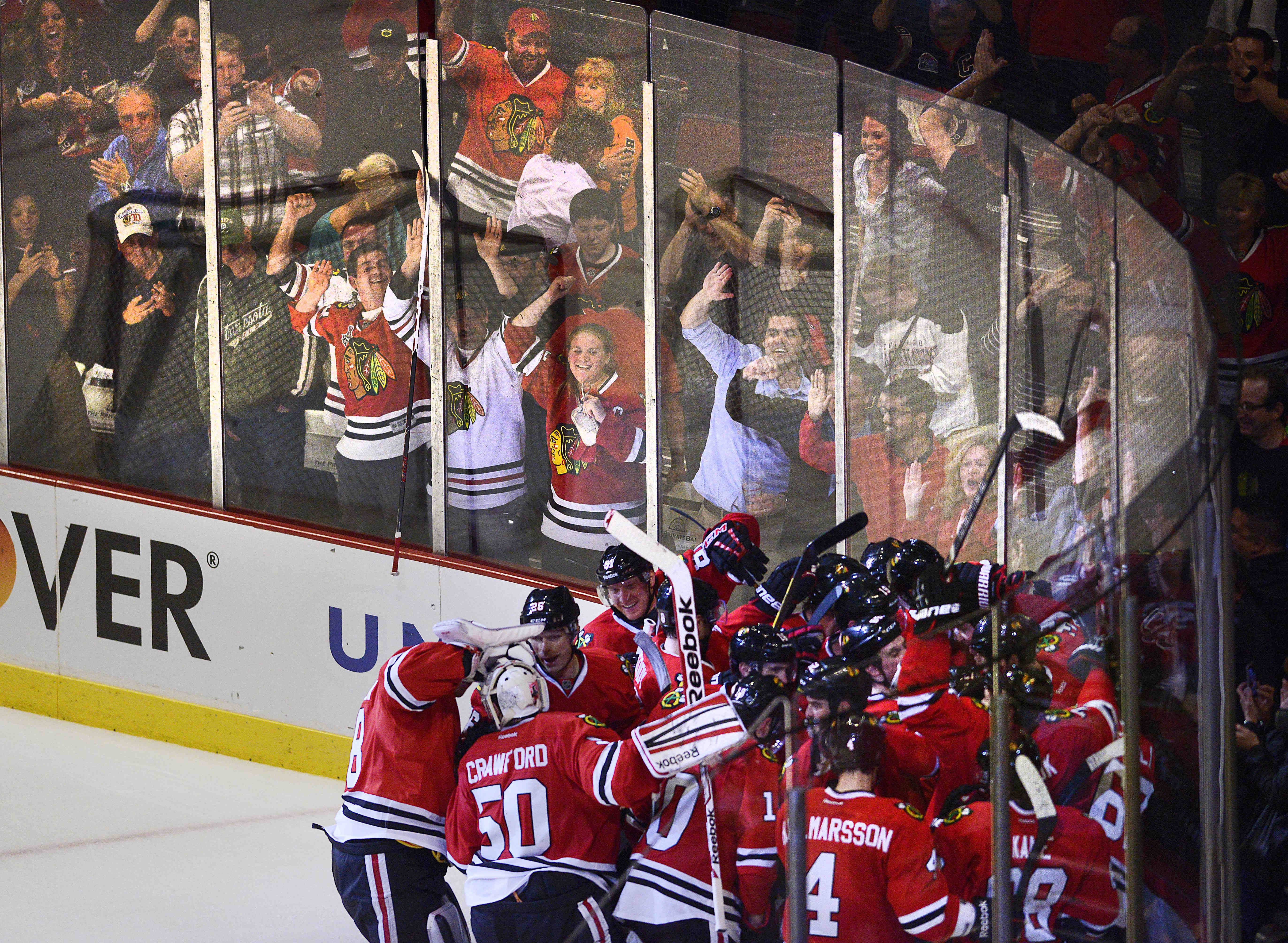 Fans celebrate behind the glass as the Chicago Blackhawks celebrate Bryan Bickell's game winner in overtime against the Minnesota Wild Tuesday in Game 1 of the Western Conference first-round playoff series at the United Center in Chicago.