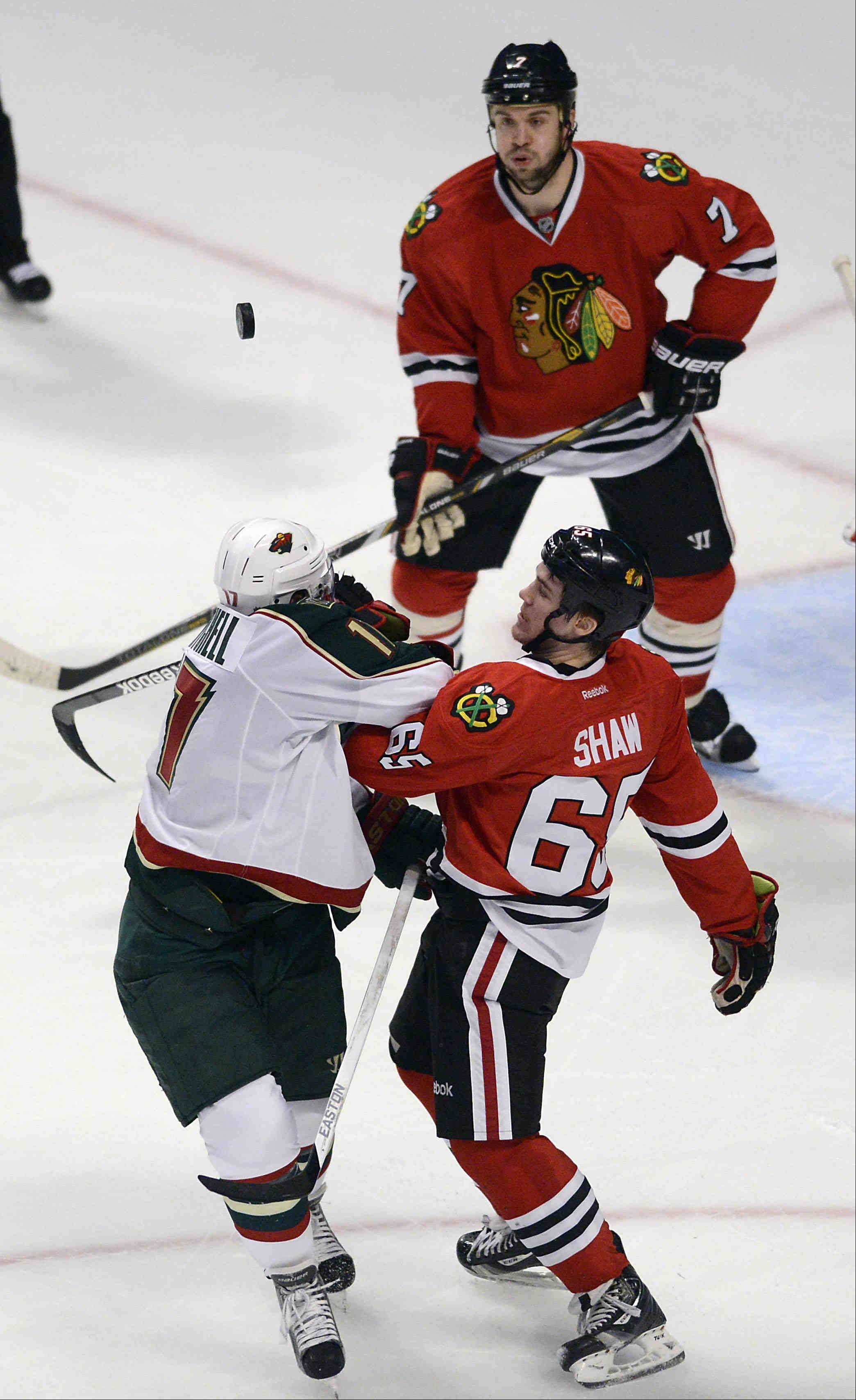 Chicago Blackhawks center Andrew Shaw and Minnesota Wild left wing Torrey Mitchell fight for control of the soaring puck as Chicago Blackhawks defenseman Brent Seabrook watches.
