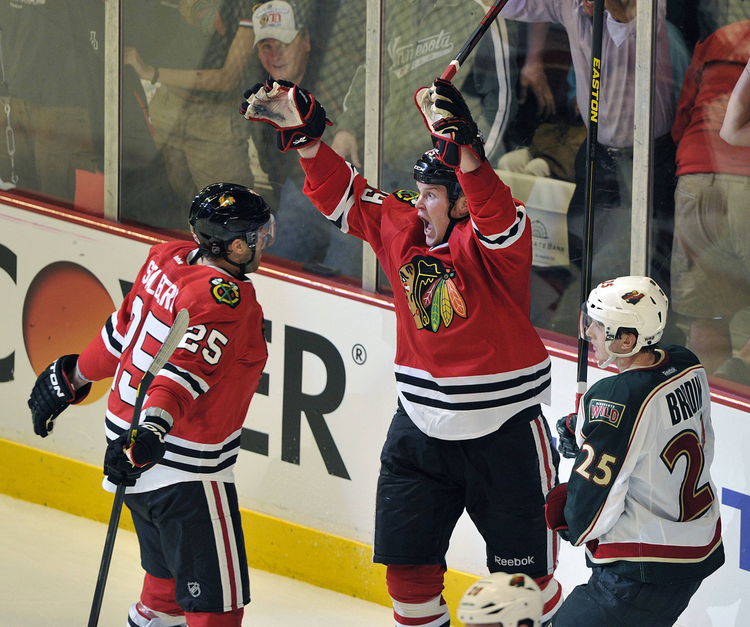 Chicago Blackhawks' Viktor Stalberg (25) celebrates with Bryan Bickell after Bickell's game-winning goal in overtime, as Minnesota Wild's Jonas Brodin (25) skates by in Game 1 of an NHL hockey Stanley Cup playoff series Tuesday, April 30, 2013, in Chicago. The Blackhawks defeated the Wild 2-1.