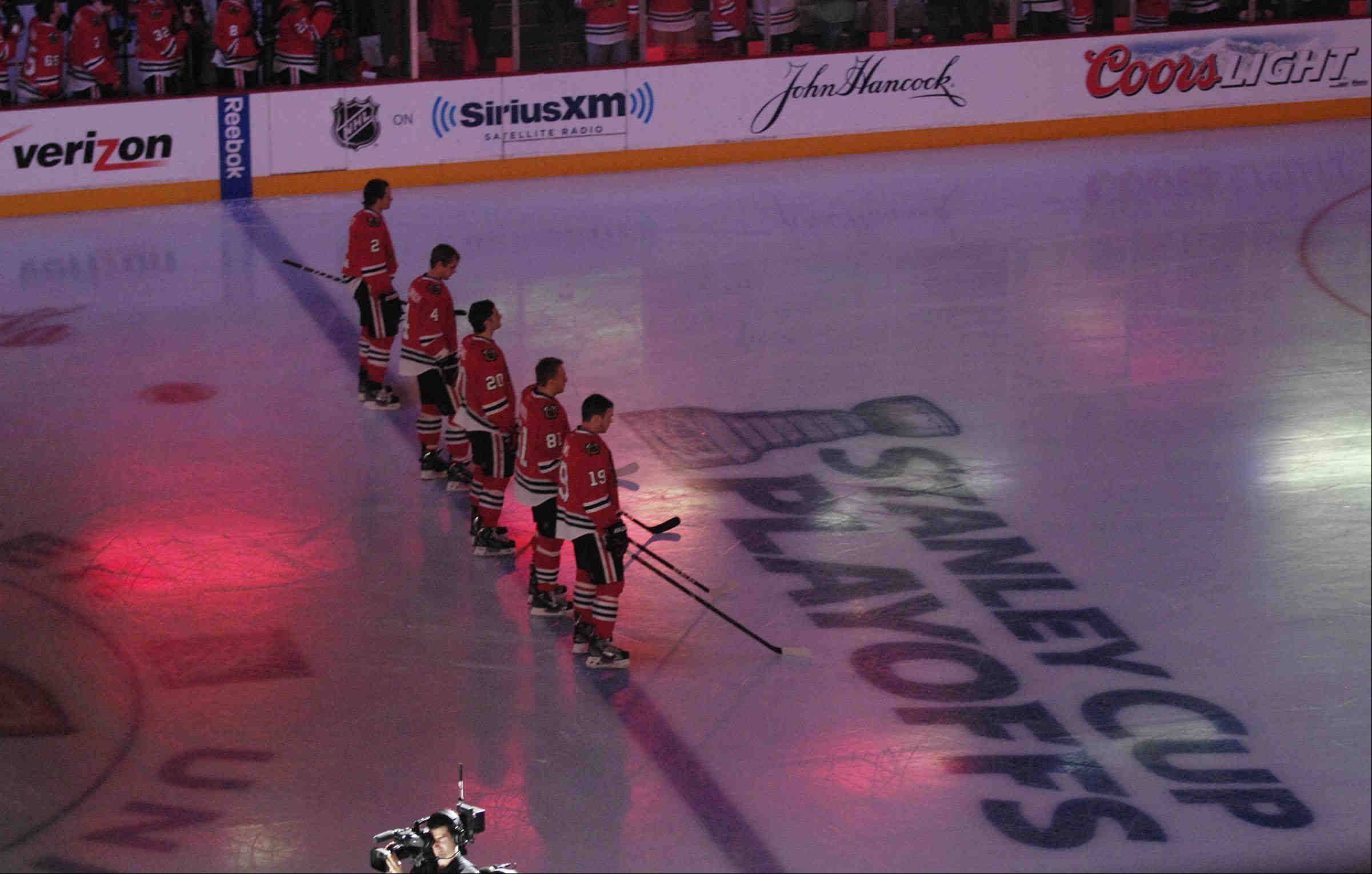 Blackhawks stand on the blue line during the National Anthem.