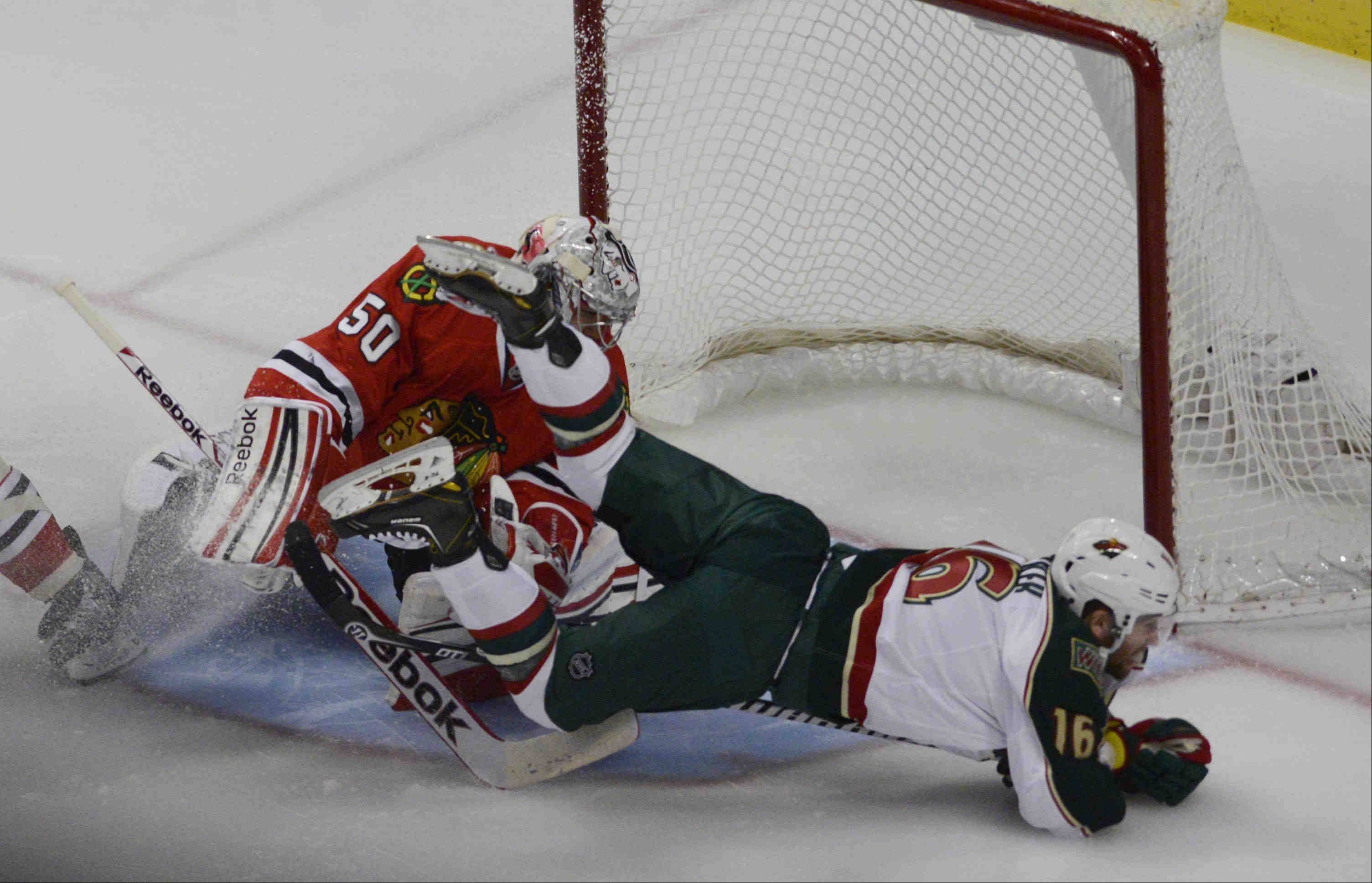 Minnesota Wild left wing Jason Zucker collides with Chicago Blackhawks goalie Corey Crawford .