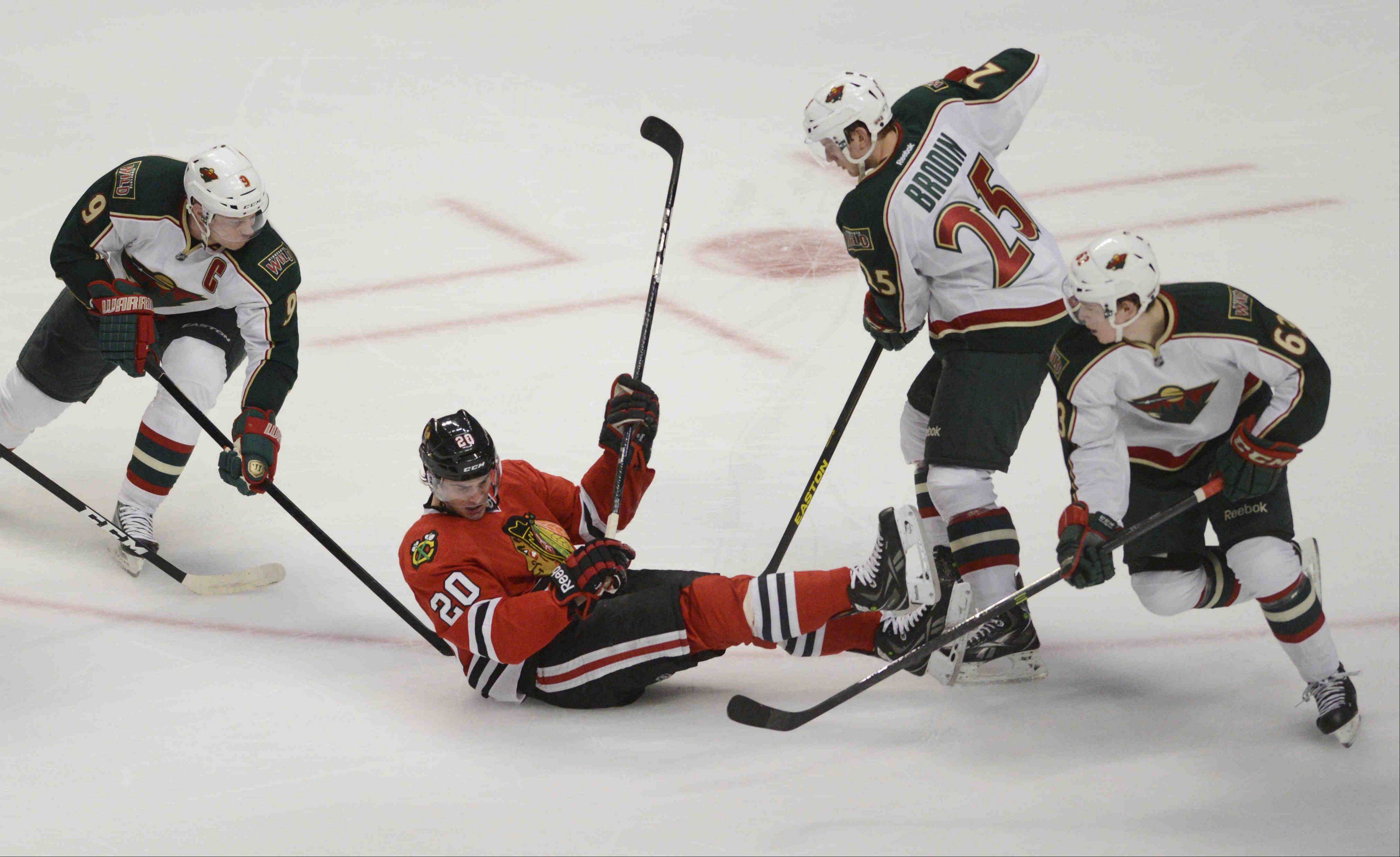 Chicago Blackhawks left wing Brandon Saad is surrounded by Minnestoa players.