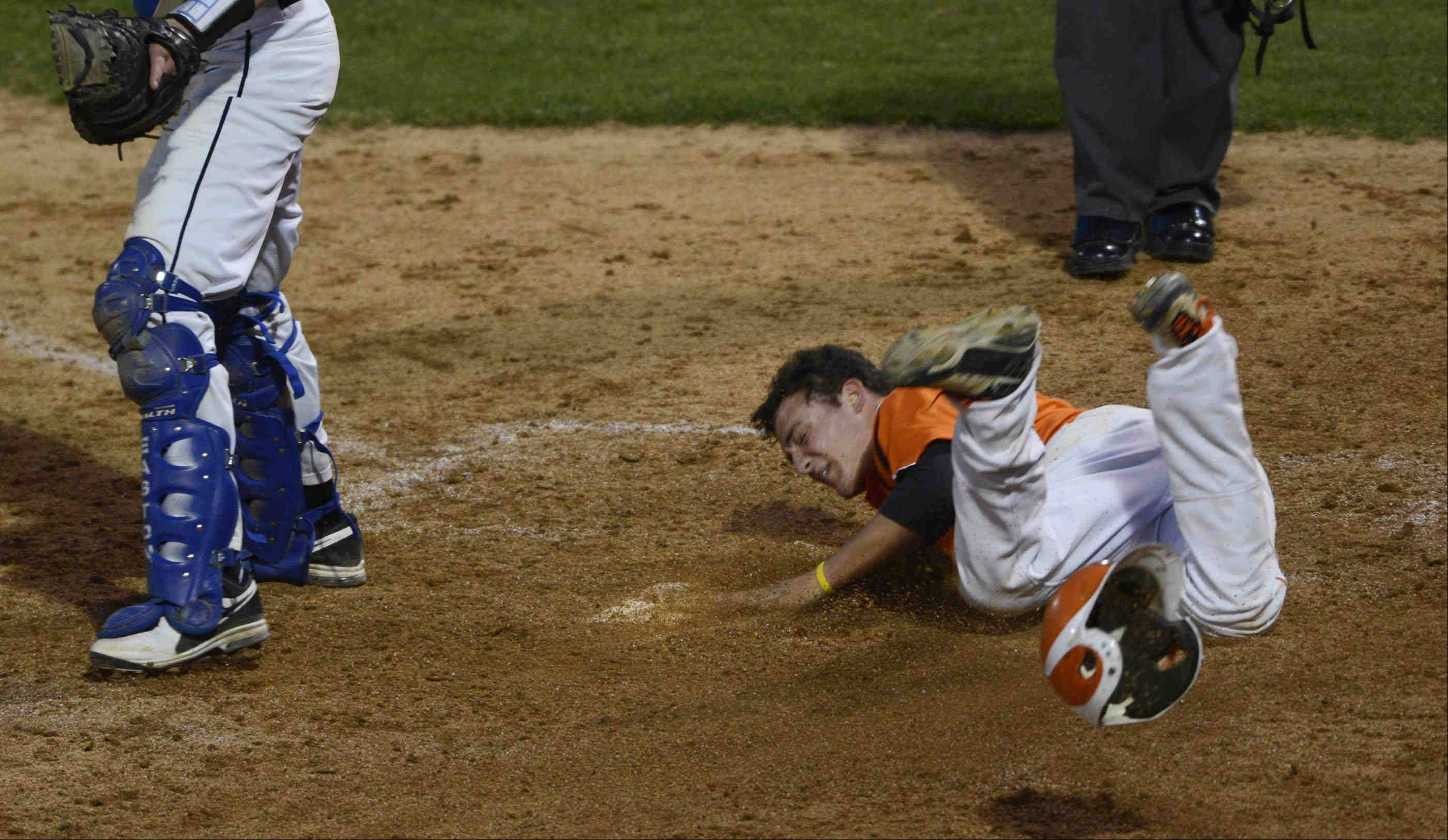 St. Charles East's Anthony Sciarrino slides over home plate in the fourth inning against St. Charles North Monday at Fifth Third Bank Park in Geneva. The score was taken off the board after an appeal by North coaches.