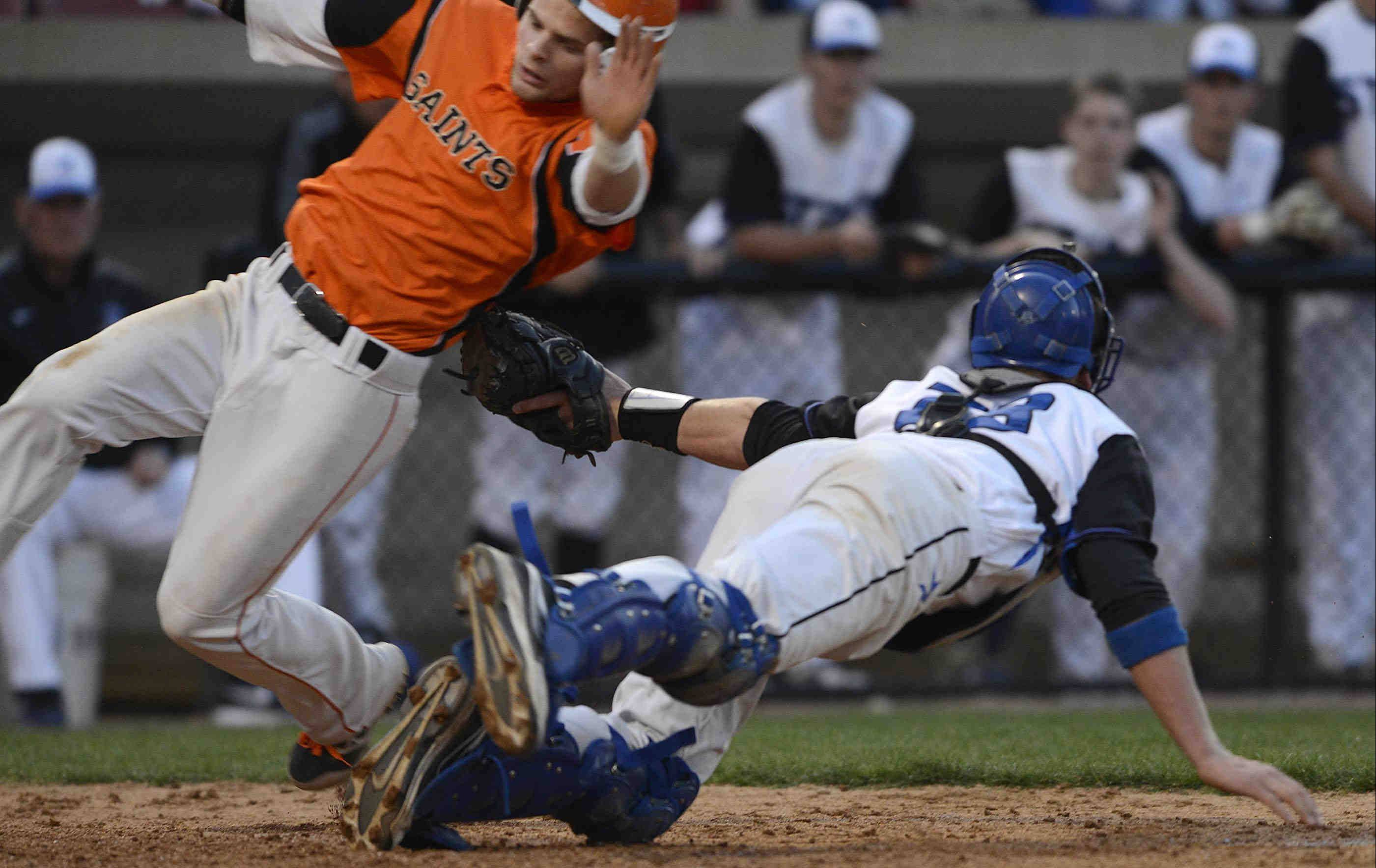 St. Charles East's Nicholas Erickson avoids the tag of St. Charles North catcher Ryan Thomas Monday at Fifth Third Bank Park in Geneva. Thomas actually did not have the ball in his glove and the Saints' Brian Sobieski also scored on the play.
