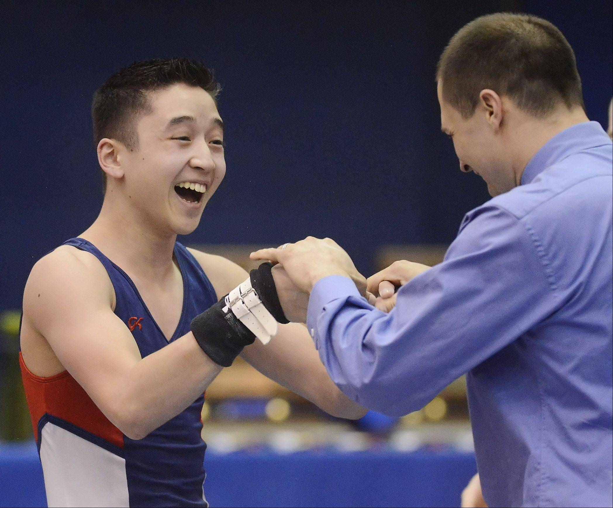 Conant's Brandon Metcalf celebrates his performance on still rings with coach Mike Opsal during the Mid Suburban League boys gymnastics meet at Hoffman Estates High School Friday.