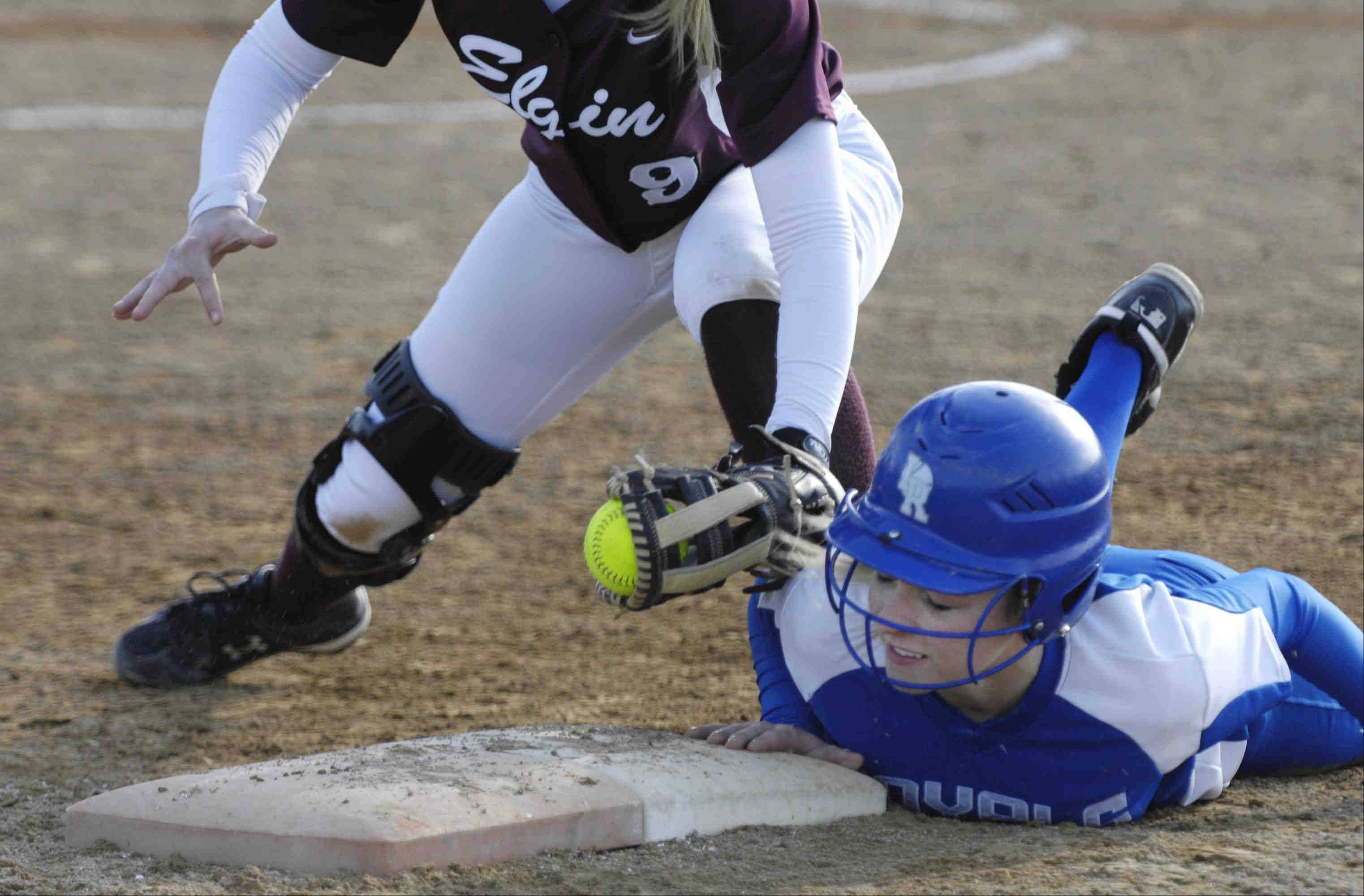 Larkin's Alexis Price dives safely back to first base as Elgin's Monica Stockman swipes the tag Wednesday in Elgin.