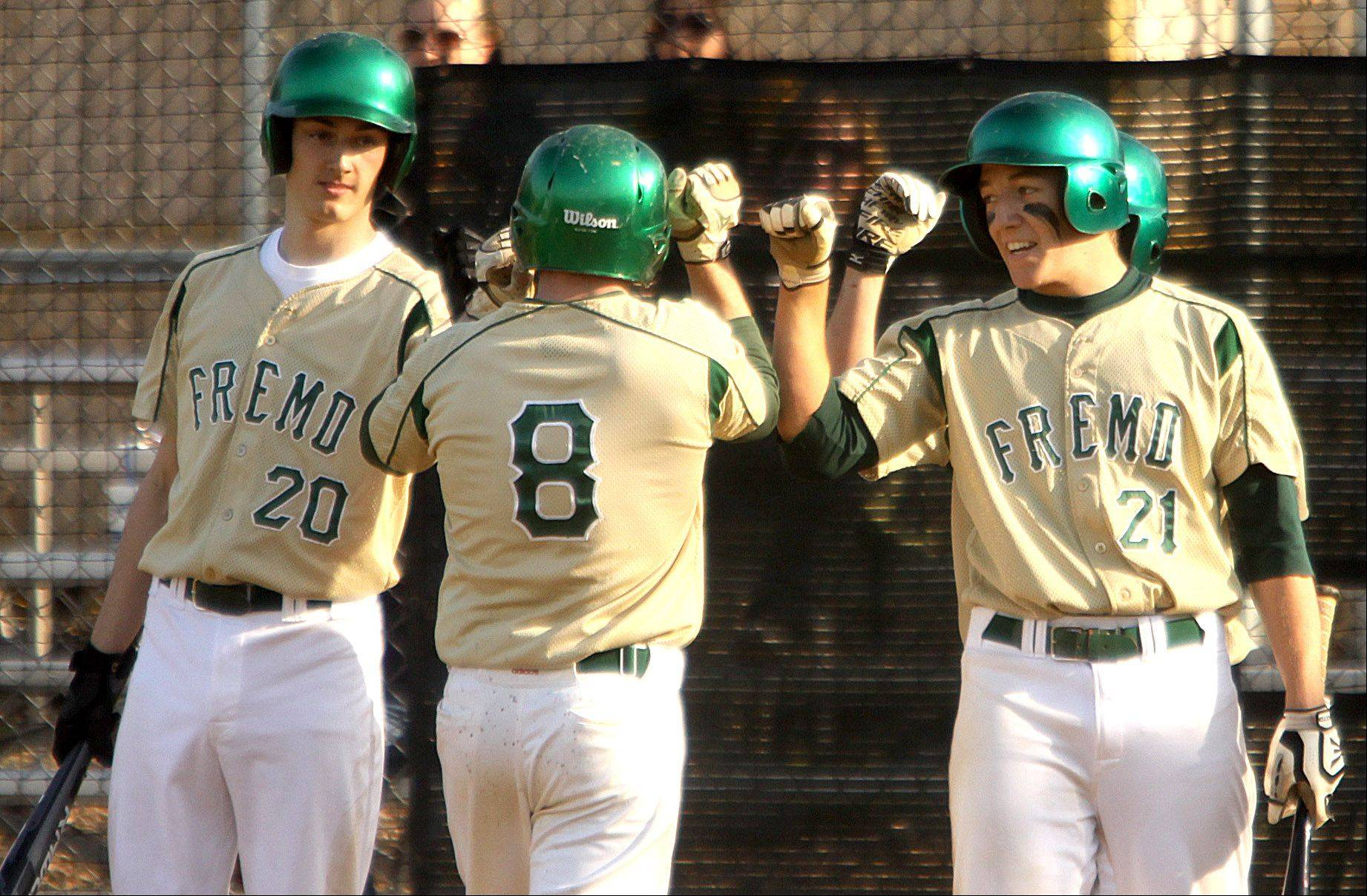 Fremd's Sam Beutler, center, is congratulated by teammates Austin Jetel, left, and Marcus Middlebrook after Beutler belted a home run against Schaumburg during Monday's baseball game in Palatine.