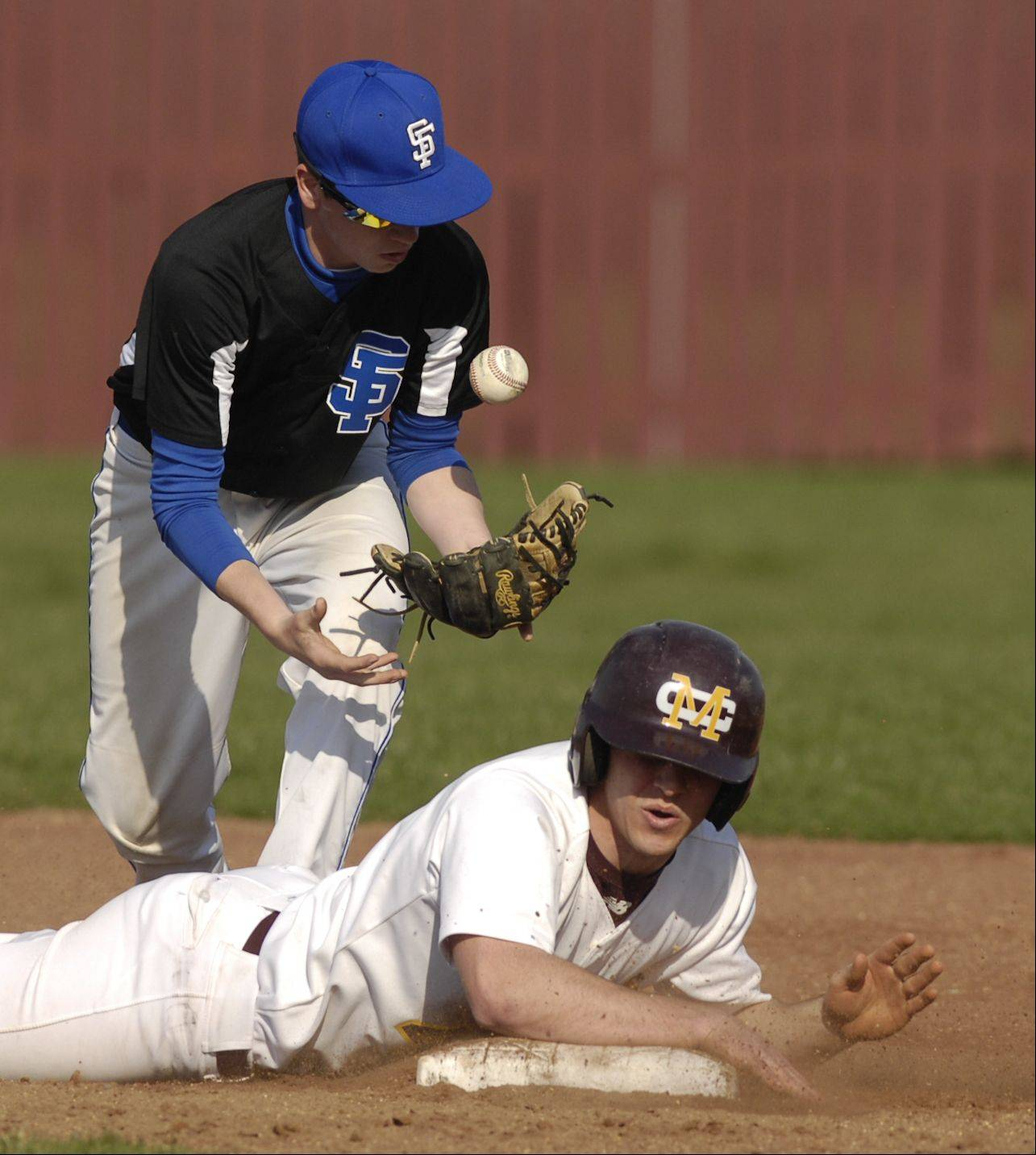 Montini's Alex Alcantara makes it back safely to second base as Jake Pestel of St. Francis bobbles the ball during Monday's baseball game in Lombard.
