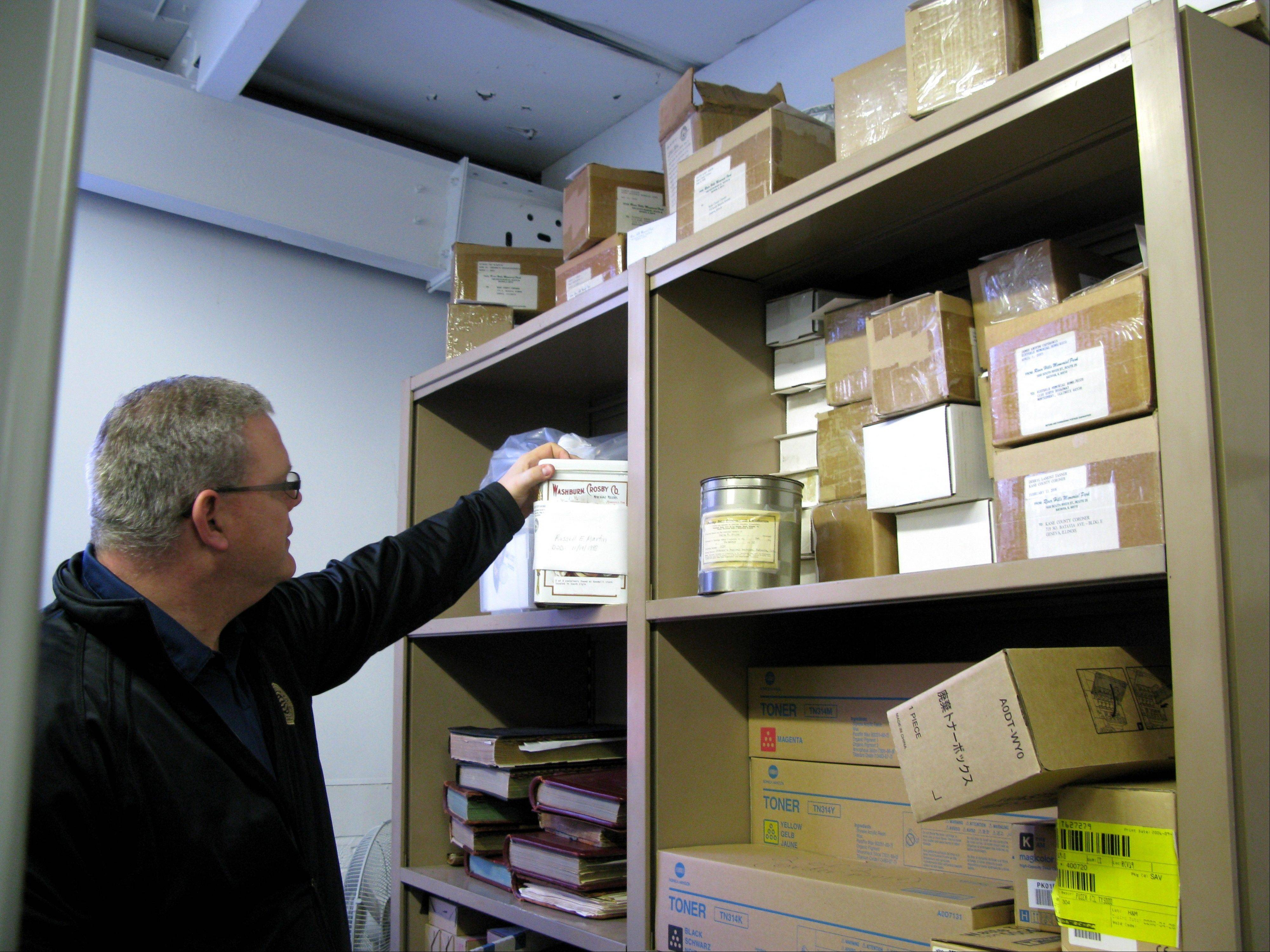 Kane County Coroner Rob Russell shows where some cremains were being stored in his office.