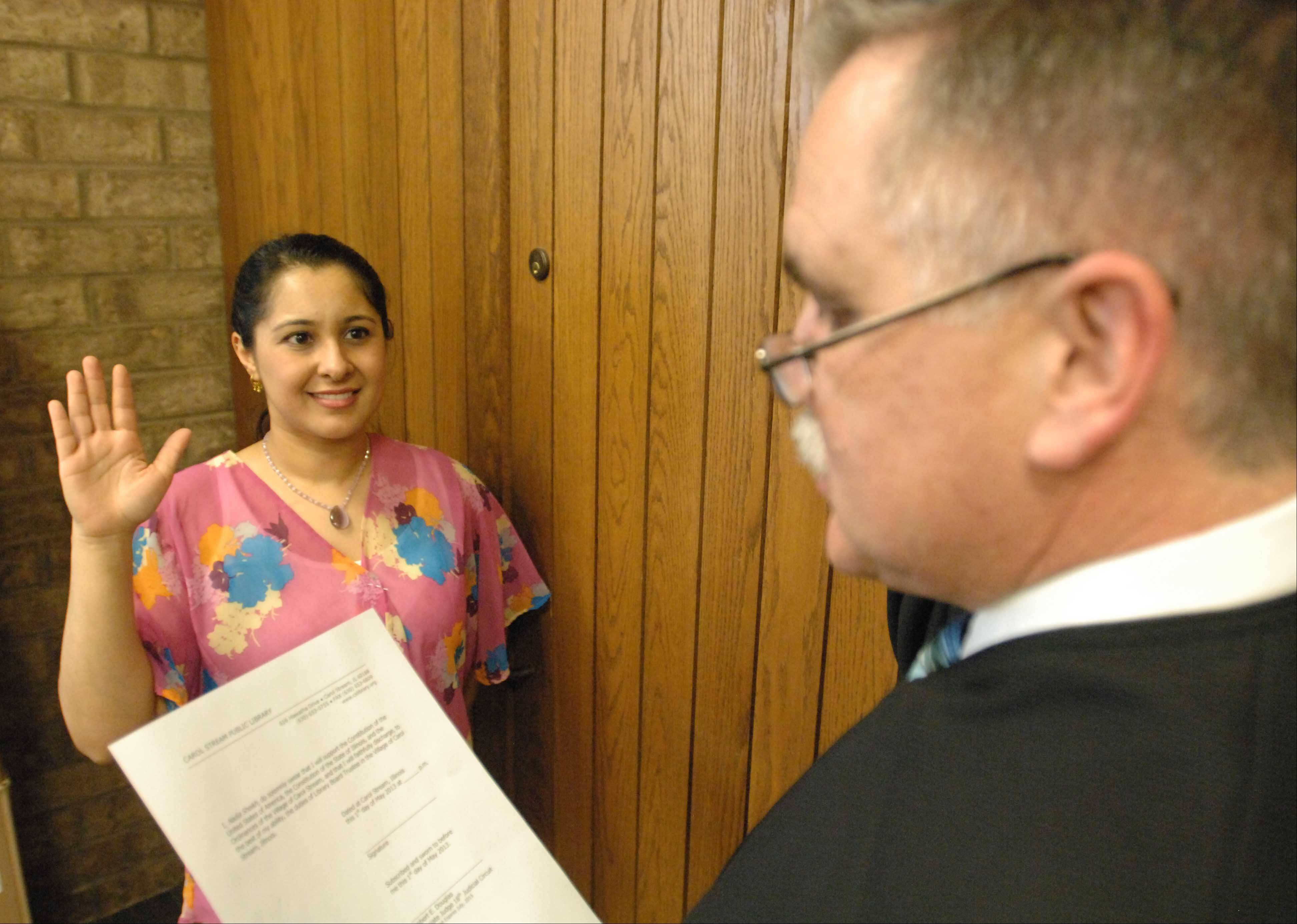 DuPage County Associate Judge Rob Douglas swears in Nadia Sheikh, one of the newly elected Carol Stream library board trustees, on Wednesday -- two weeks earlier than scheduled so the new board could prevent the outgoing board's attempt to sell the library's Kuhn Road property.