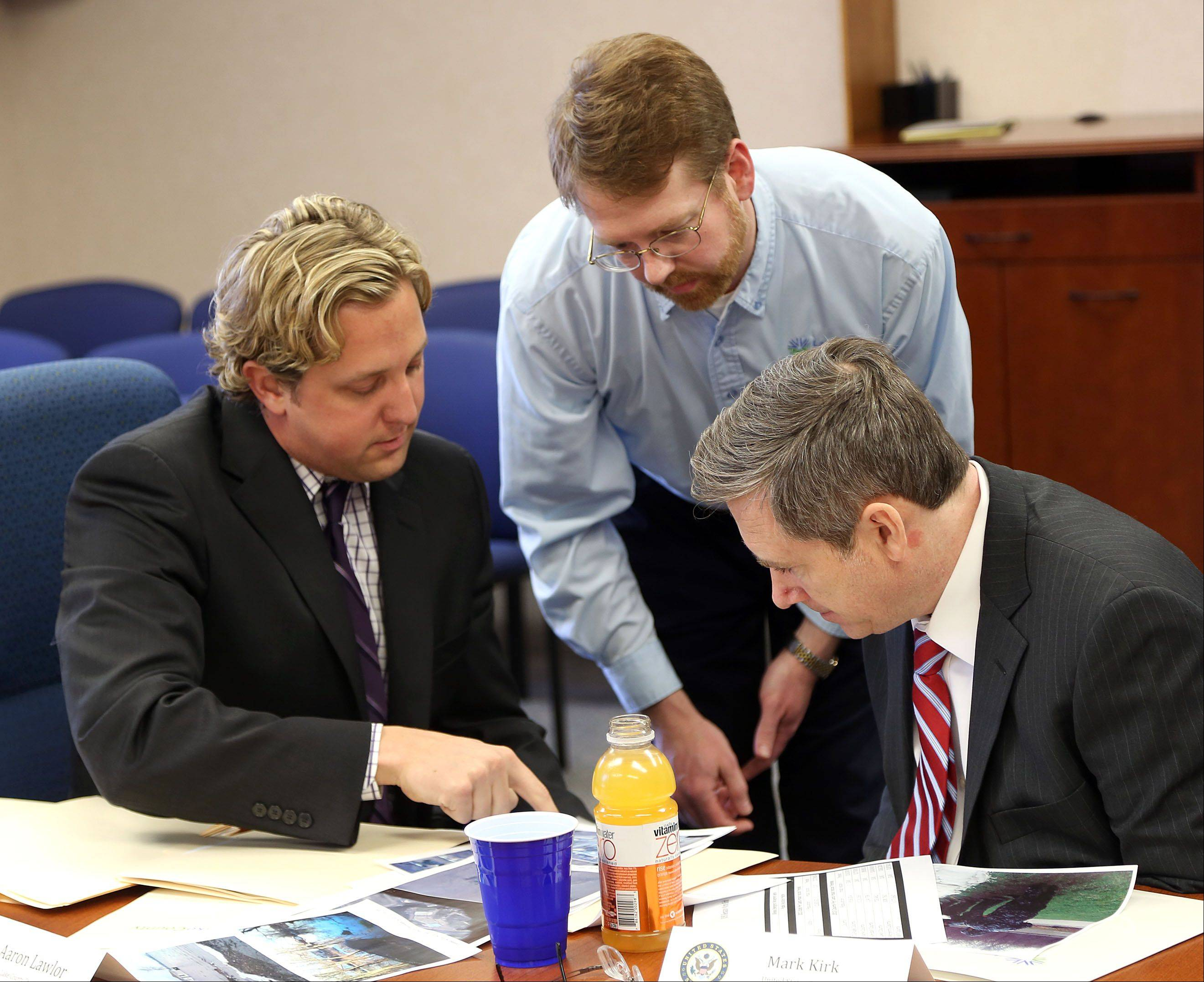 U.S. Sen. Mark Kirk, right, Lake County Chairman Board Aaron Lawlor, left, and Lake County Emergency Management Coordinator C. Kent McKenzie look over maps of flooded areas during a meeting at the Lake County Division of Transportation in Libertyville Wednesday.