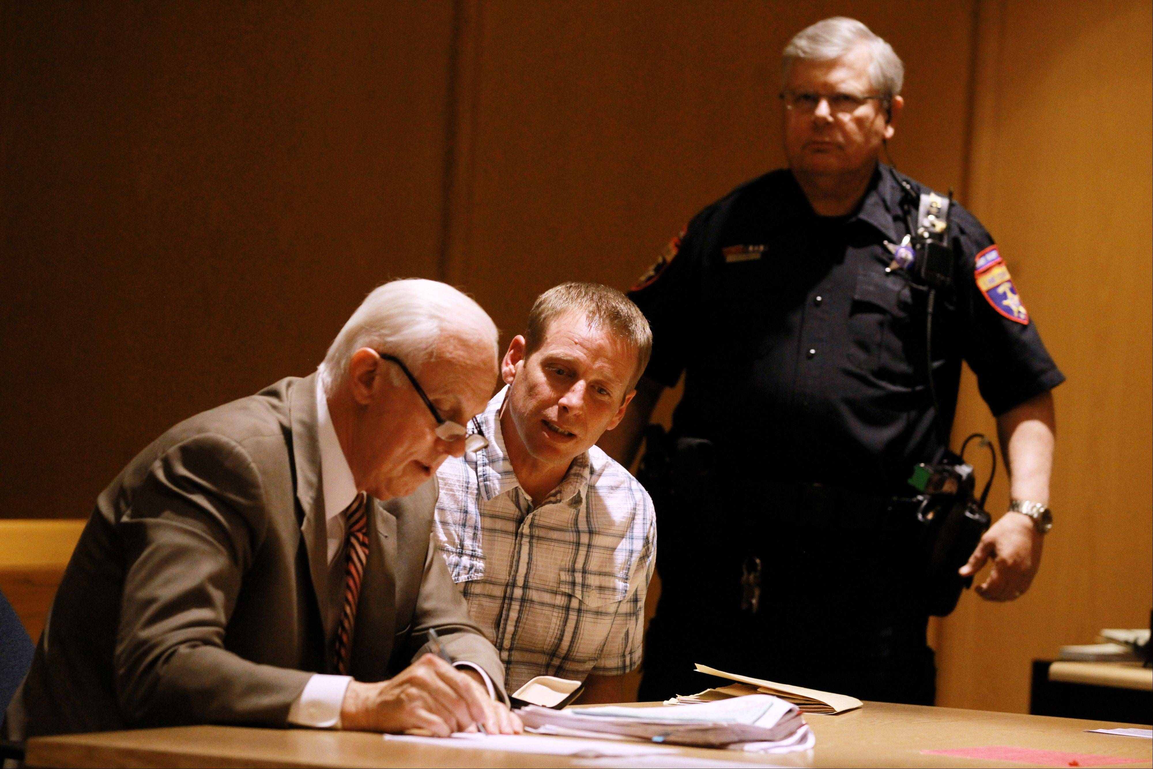 Timothy Morrow, 43, of Round Lake Beach, center, speaks with his defense attorney, Mike Norris, left, after being sentenced Wednesday to 13 years in prison for an eighth DUI conviction.