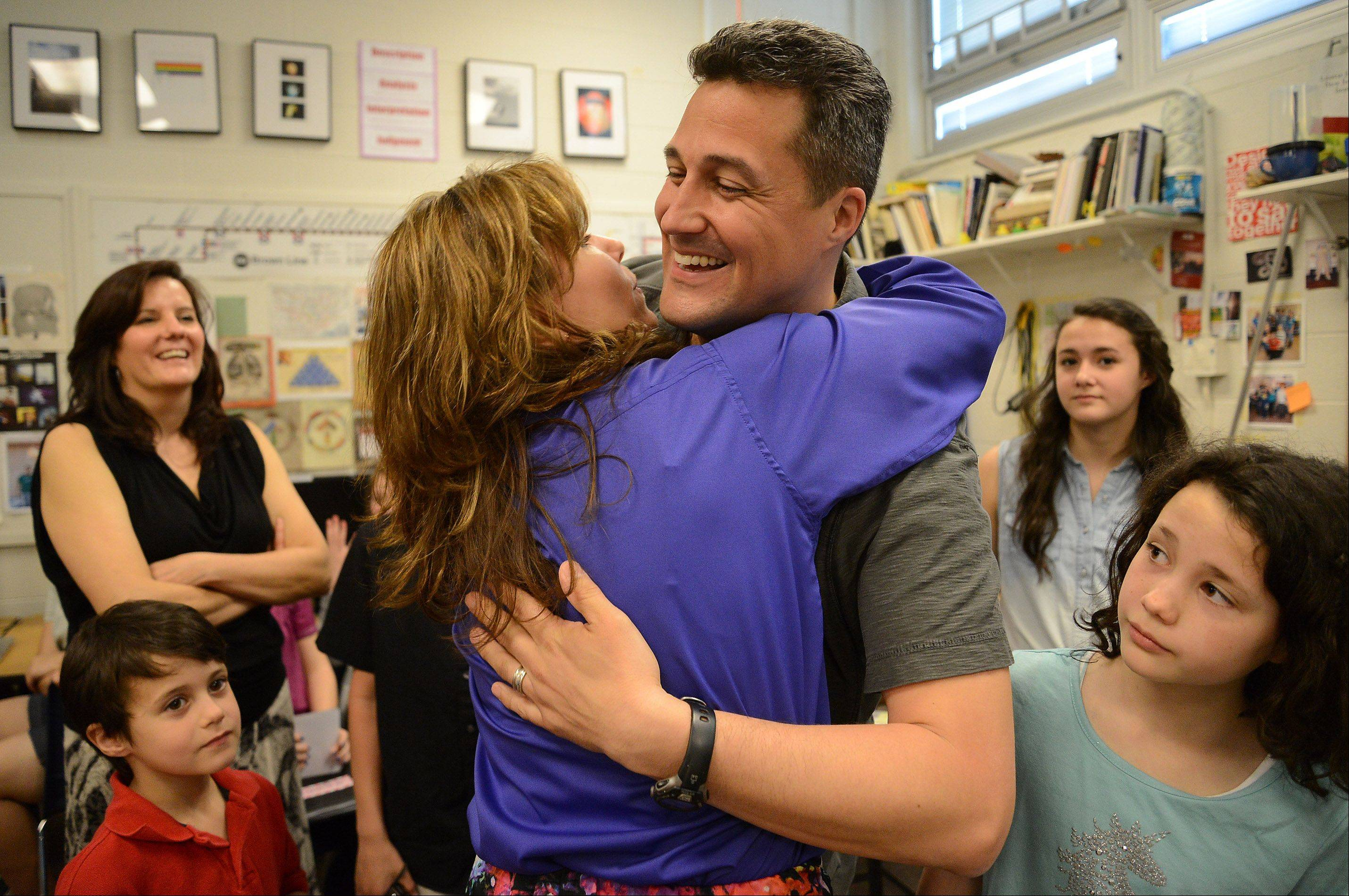 Gregory Regalado, who teaches art, photography and advanced digital imaging at Maine West High School in Des Plaines, gets a hug from Principal Audrey Haugan after being surprised in his classroom Wednesday by Golden Apple representatives.