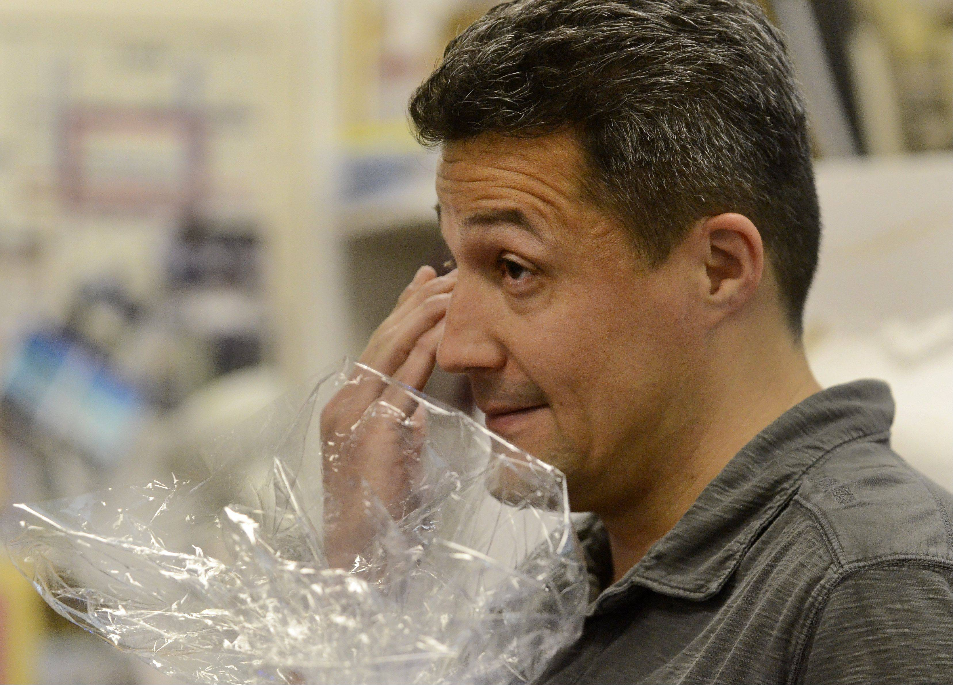 Gregory Regalado, who teaches art, photography and advanced digital imaging at Maine West High School in Des Plaines, tears up after being surprised in his classroom by Golden Apple representatives.