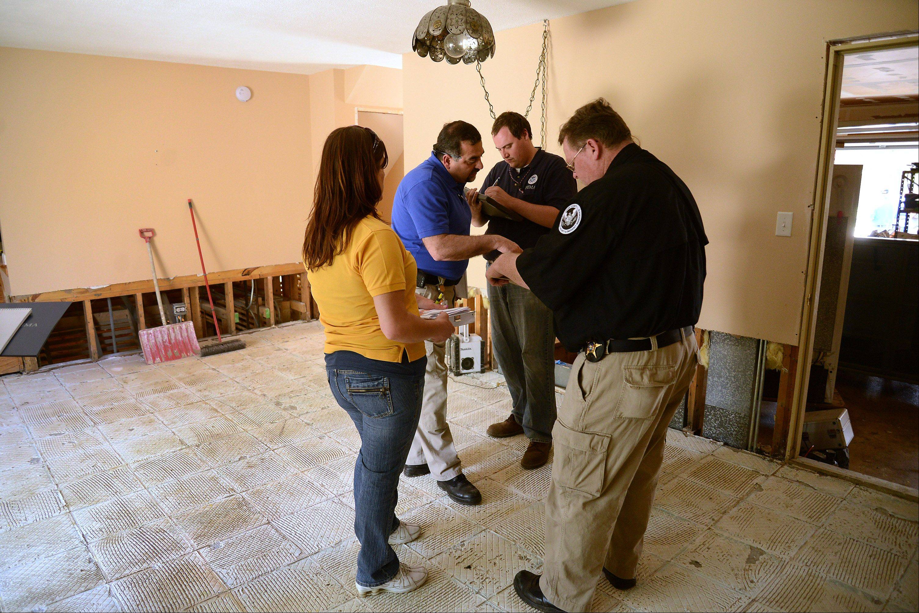 FEMA workers tour a home on Big Bend Drive in Des Plaines on Tuesday to assess the damage from the recent flood.